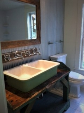 This bathroom was so fun to put together.  The walls are corrugated roofing metal (galvanized).  We found the antique sink at a salvage yard and we placed it atop an antique workers bench we found on the property.  Plumbing fittings come out of the wall and towel bar is made from pipe fittings.