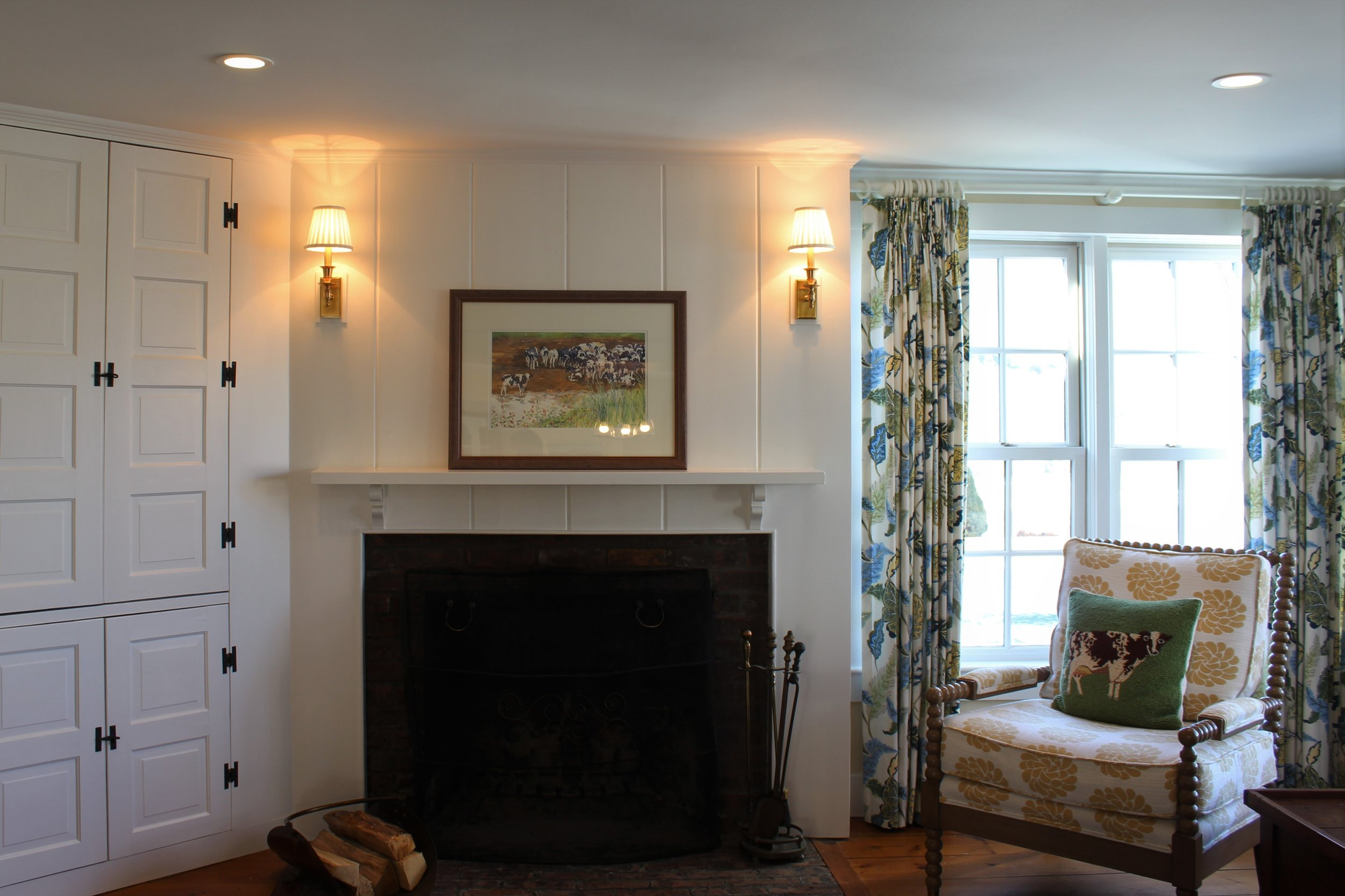 The fireplace is the antithesis of the one above. This is over 100 years old and in an antique farmhouse. The owner wanted to keep the simplicity of the original simple mantle and paneled wall. This allowed us to bring pattern into the room with drapery panels and the spool chair fabric. We added simple brass sconces to frame the artwork and bring light into the space at night.