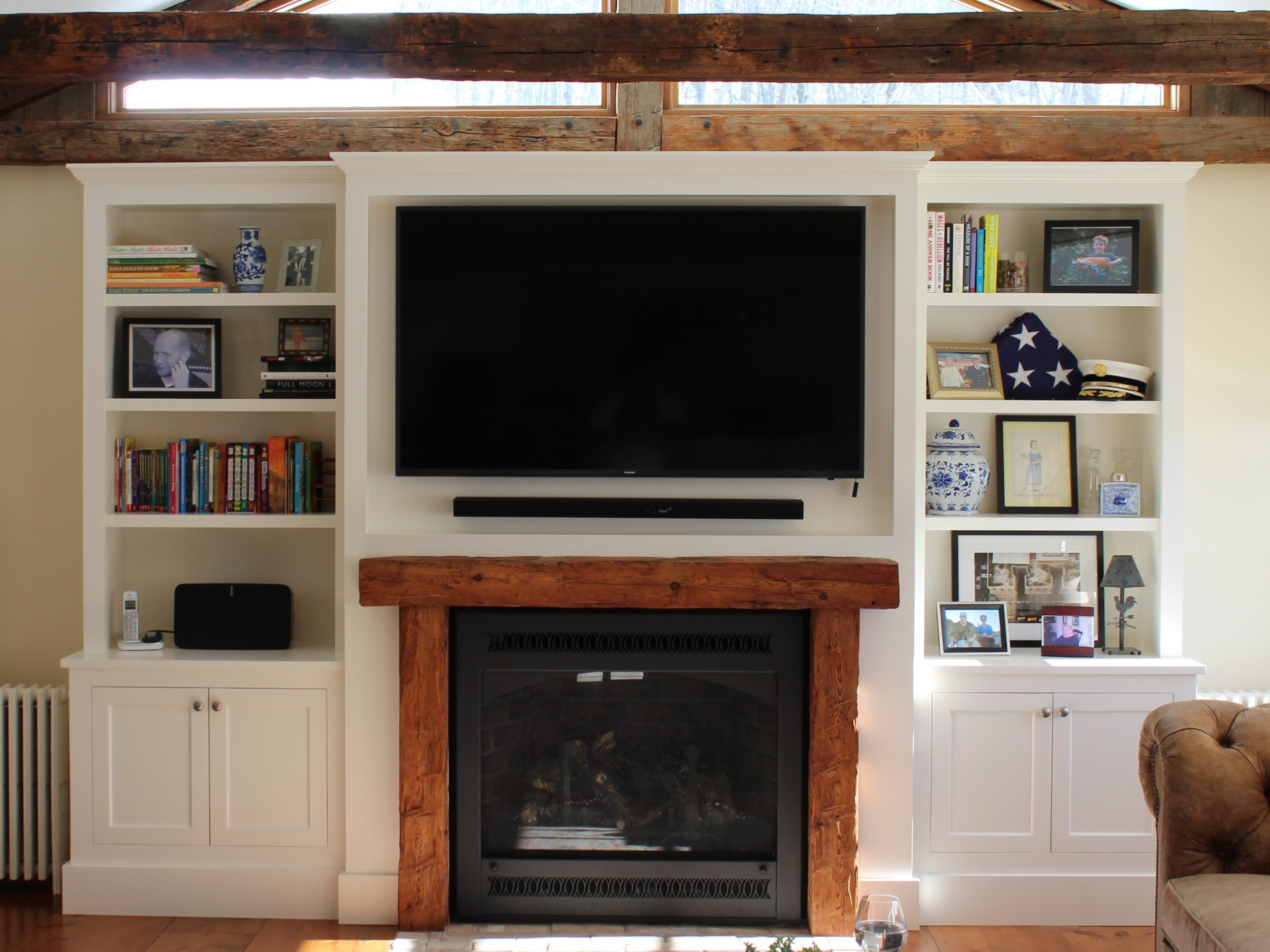 """What do you do when you want a fireplace but don't have a wall to put it on? Choose a gas insert either """"vent-less"""" or a """"direct vent"""". This client had only a TV on this large wall, but wanted a fireplace and a more cozy feel. We designed the built in bookcases to perfectly frame the TV and house a direct vent gas fireplace unit. The builder found the old beams to make the mantle. We are happy with how this turned out and so is the client!"""
