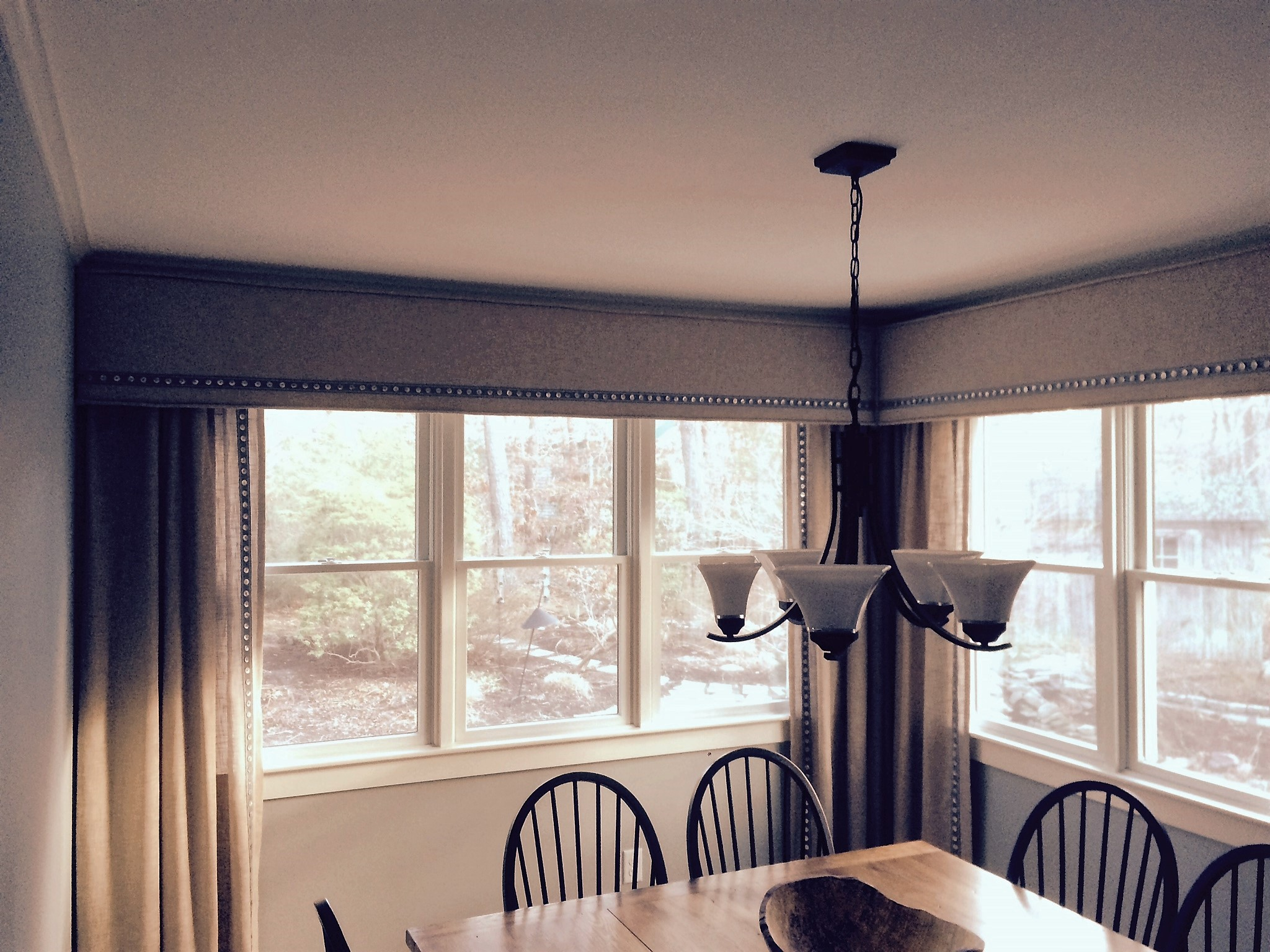This client never intended to pull the drapes shut. Our intention is to soften the space with panels at either end of the matched cornices. We doubled the panels in the corner to make it look like you could shut them if you wanted to. The decorative trim on the leading edge of the panels is a nice touch.