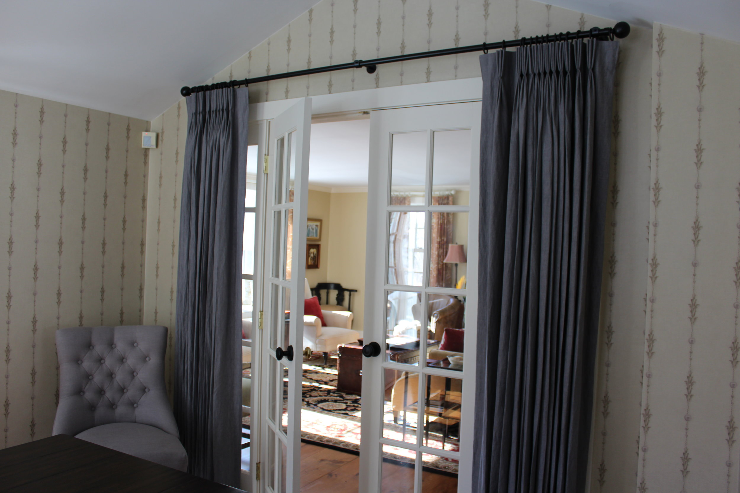 Panels are useful on interior french doors for privacy. In this dining room we treated these doors like we did the windows with linen pinch pleat drapes hung from iron rods and rings that match the door hardware.