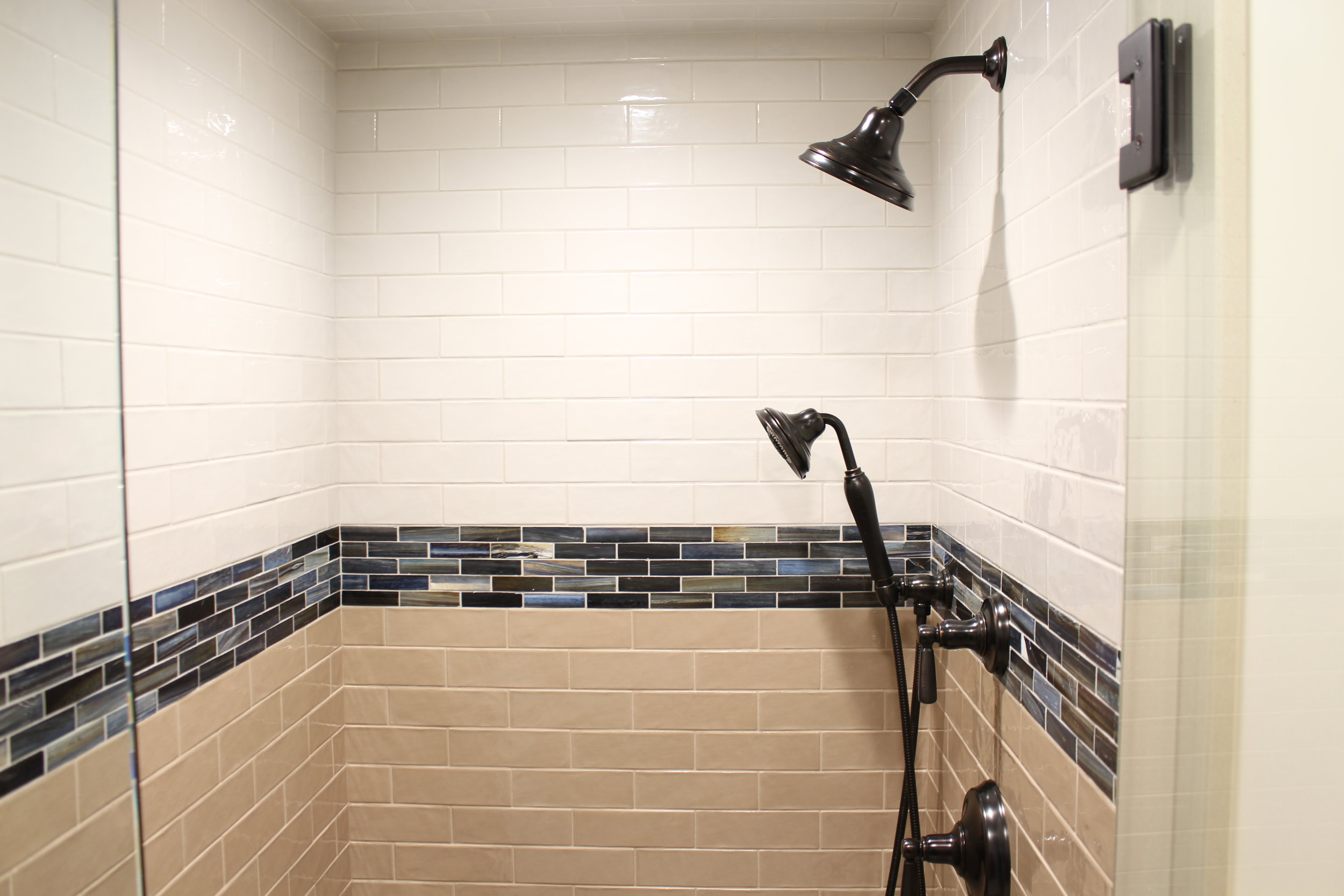 This small bathroom had room for a shower but no tub. The entrance to the shower is all glass. This along with the darker tile on the lower half of the walls makes the space feel bigger. We added a handheld shower for easier cleaning.