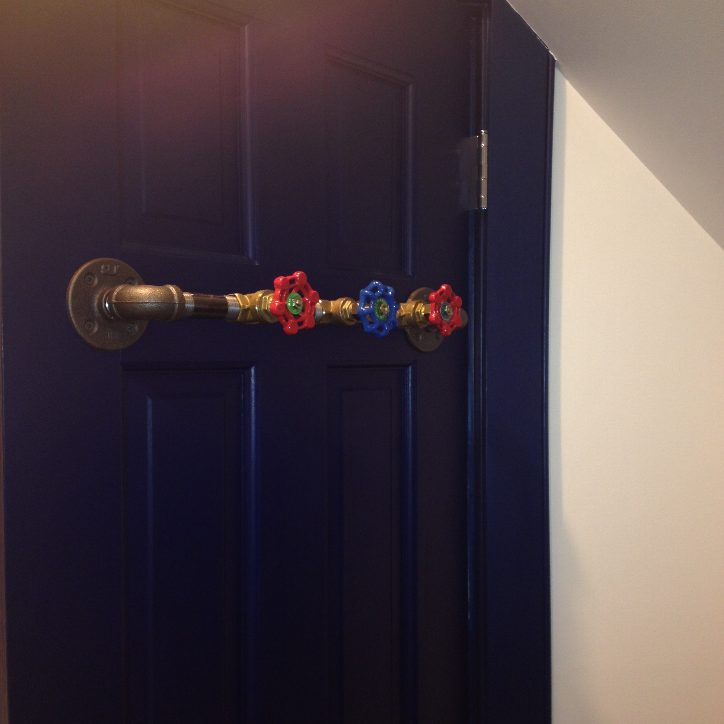Low on wall space for towel bars? How about adding robe hooks to the back of the door? We had fun in this boys bathroom and used pipe fittings to create this sturdy towel holder.