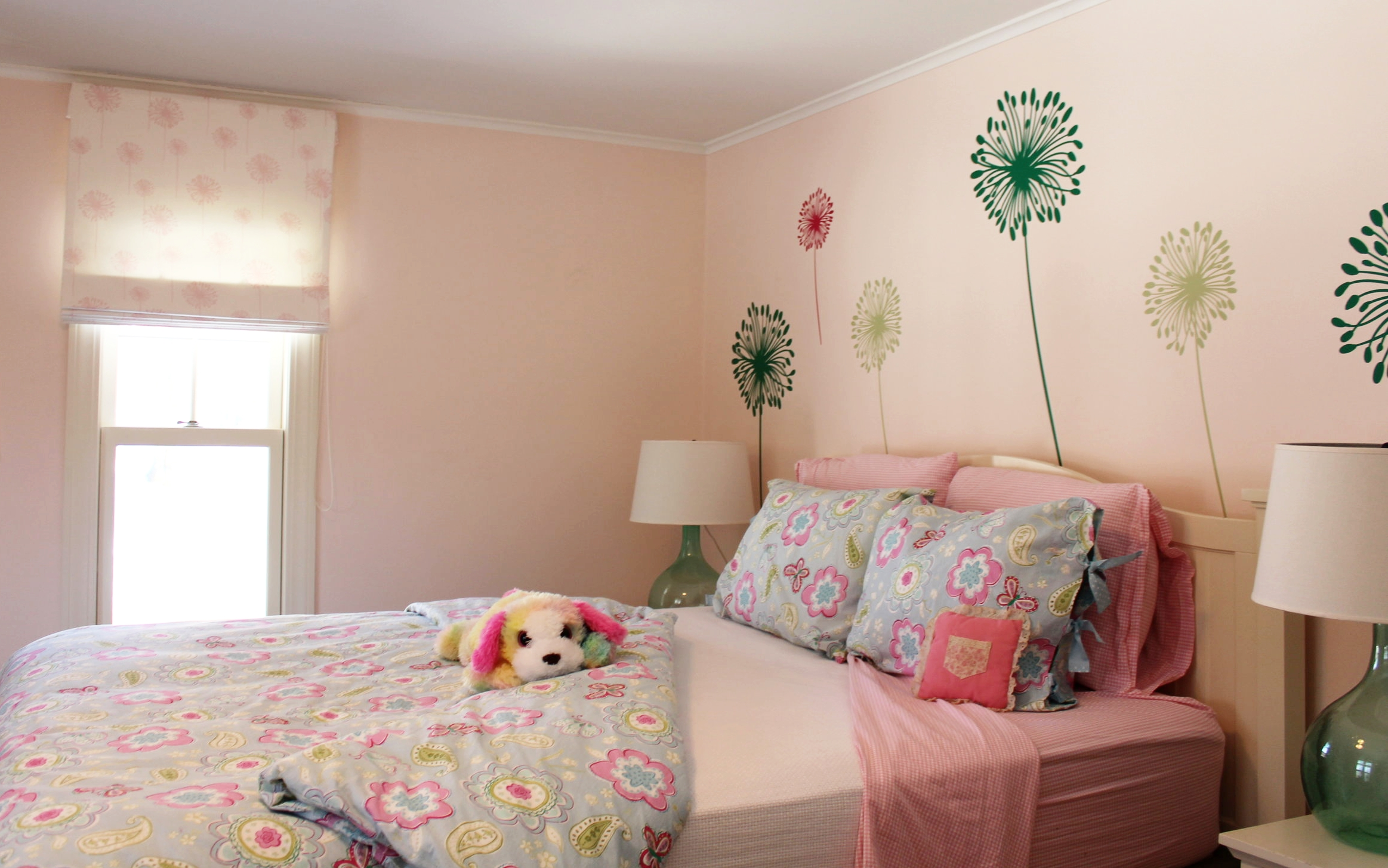 We decorated this room for a 2nd grade girl.  The dandelions on the wall are custom, and can be re-positioned or removed very easily.  They mimic the dandelions in the shade fabric ( Duralee  Fabric).  With a few tweaks (stuffed animals) this room can easily take this young lady through her middle school years.