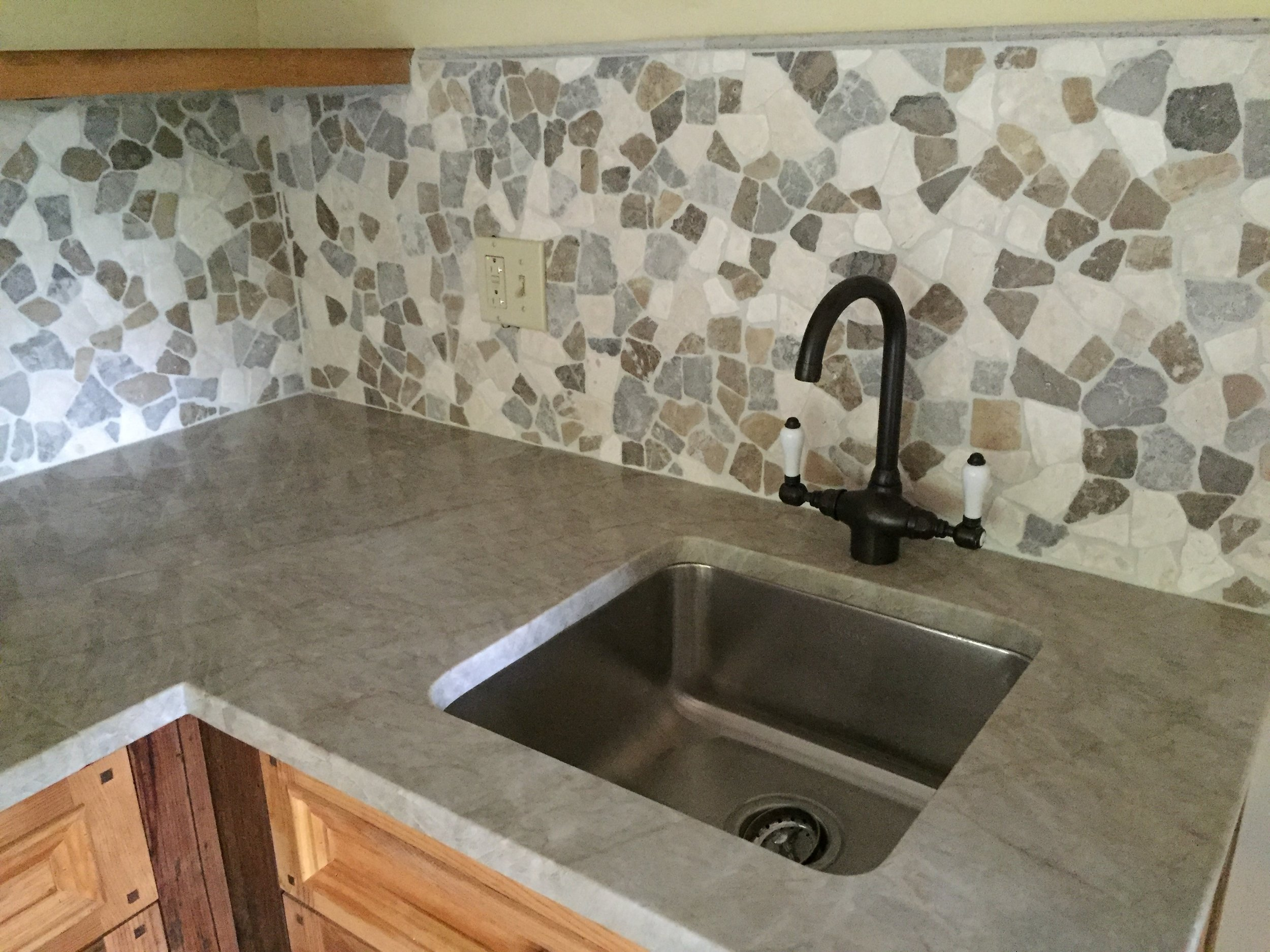 Here is a broader view of the picture above. This small kitchen is in a post and beam guest house. There are a lot of natural elements in the space and we wanted that to hold true for the kitchen. The natural stone top and back splash are a perfect complement to the rest of the guest house.