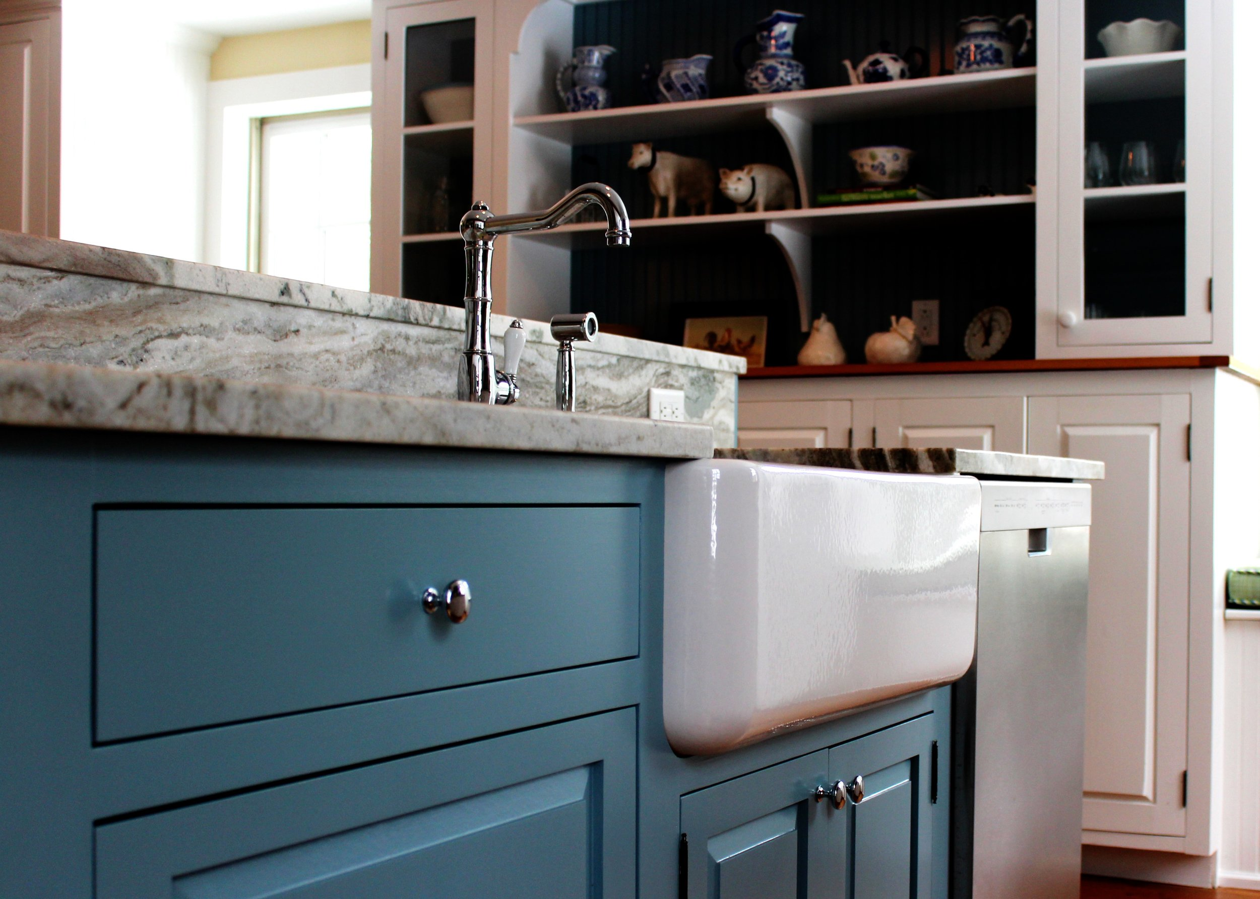 This farmhouse sink is in an island with a breakfast bar. Both the island and the breakfast bar have the same stone top. We book matched the slab for the back splash. Not only is it functional, it's beautiful!