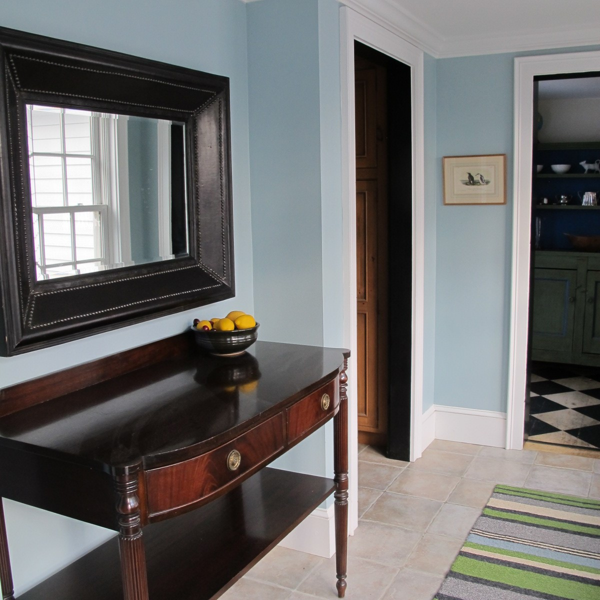Leather wrapped mirror over the small mahogany sideboard are just a few extras in this bright foyer.