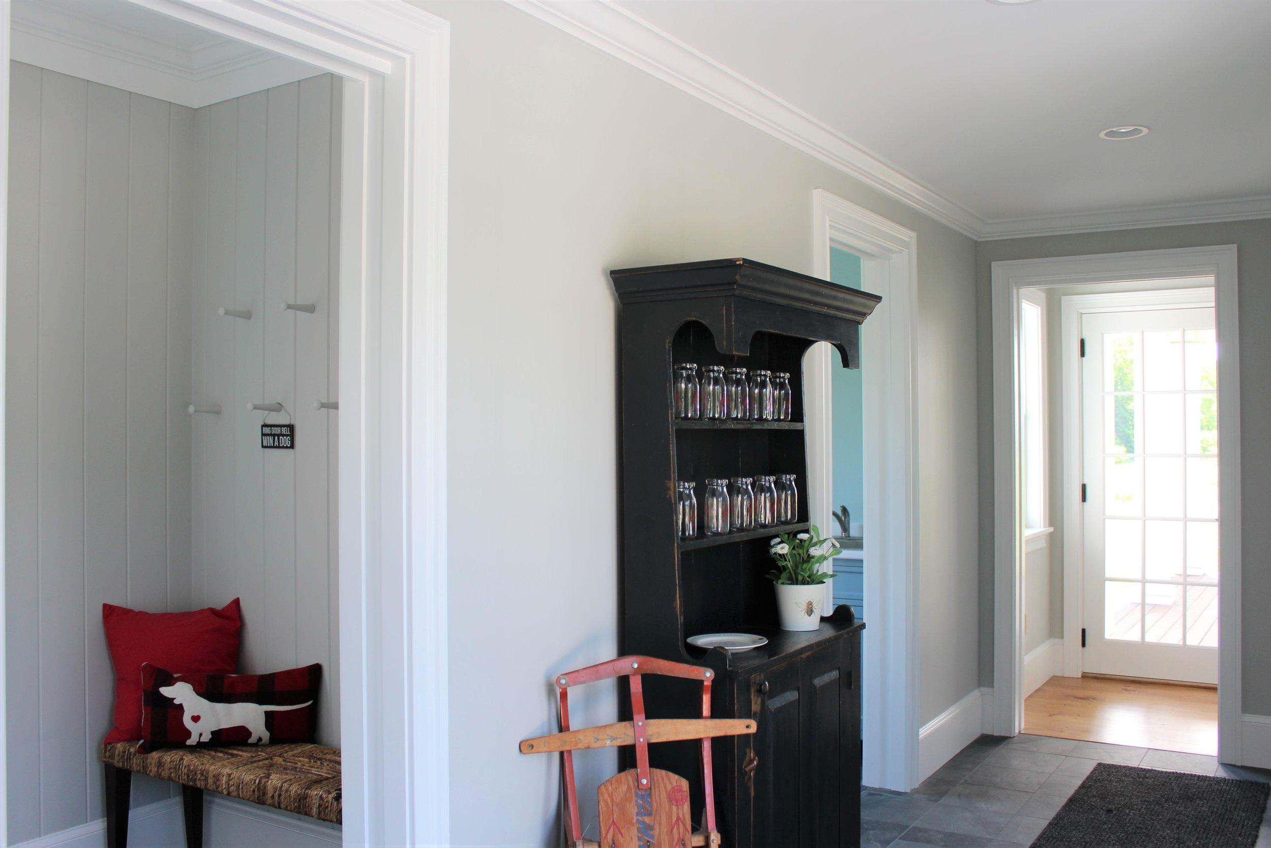 This large foyer has a separate mud room complete with a bench and pegs. The walls are v-grove panels painted the same color as the foyer, Benjamin Moore's Stonington Grey. The difference in texture adds visual interest.