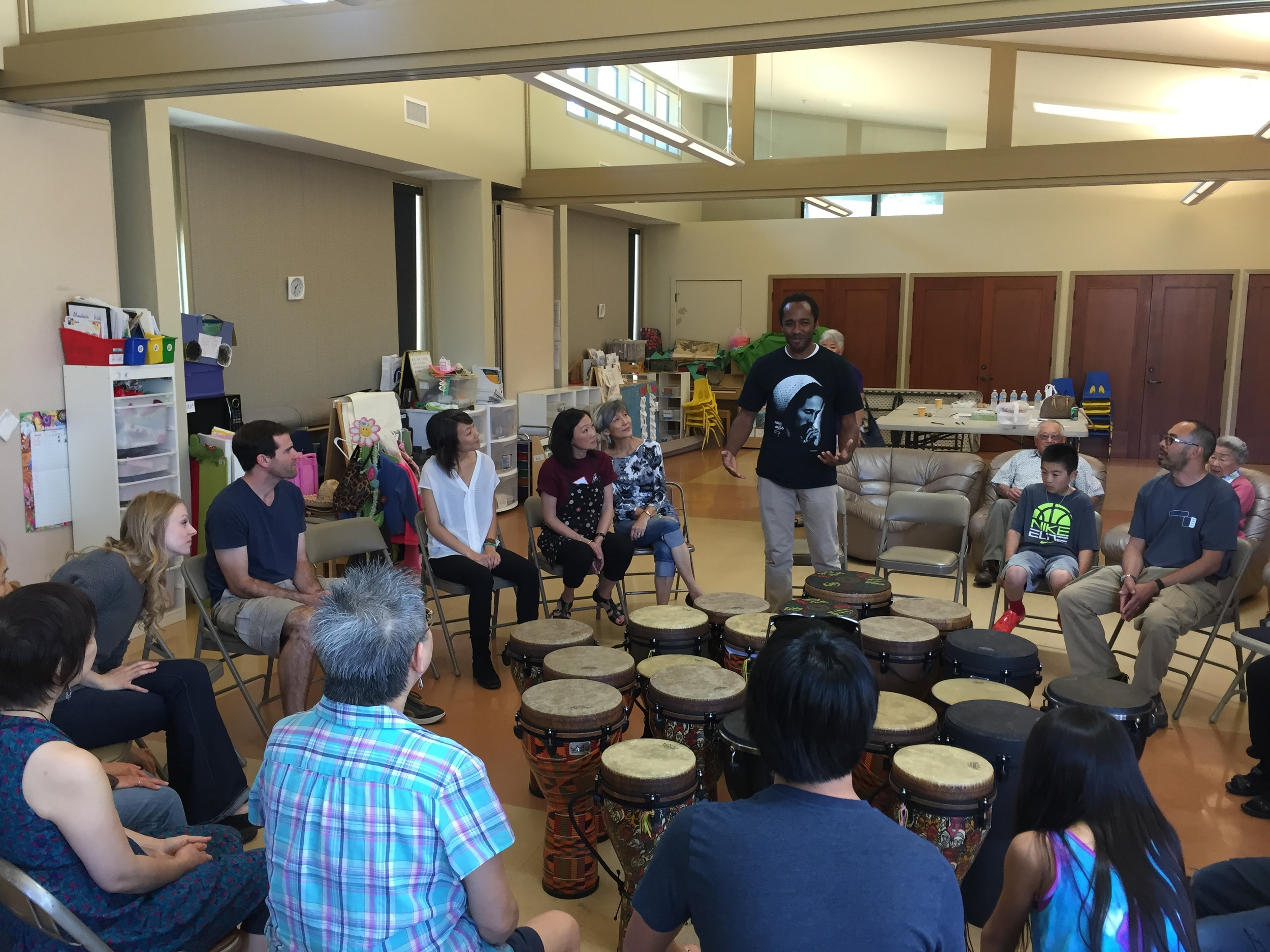 Sekayi Edwards (Creative Expression Director, standing center) begins the intergenerational group drumming circle