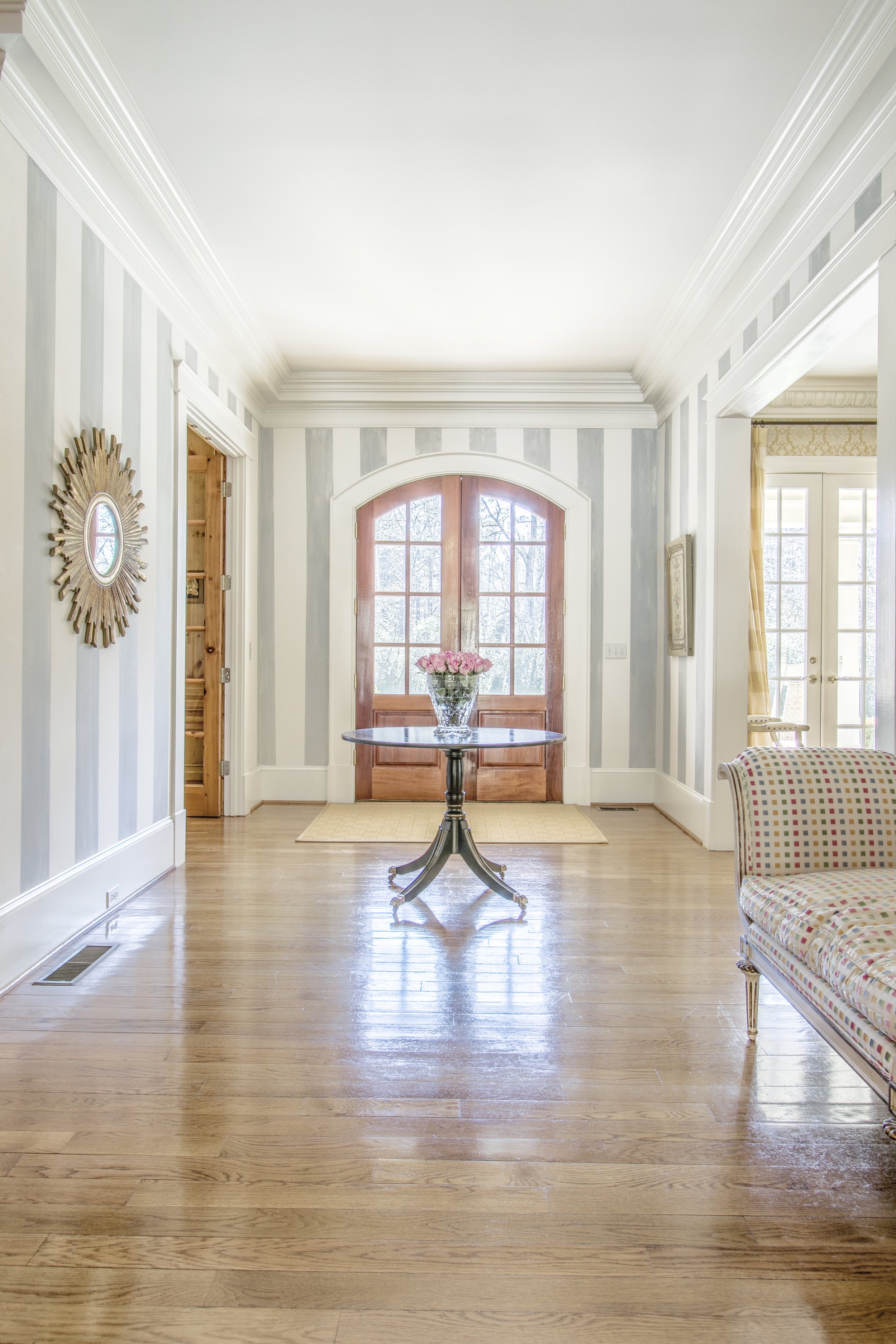 Entry Hall with striped wallpaper and flowers and a round table.  Sunburst Mirror.