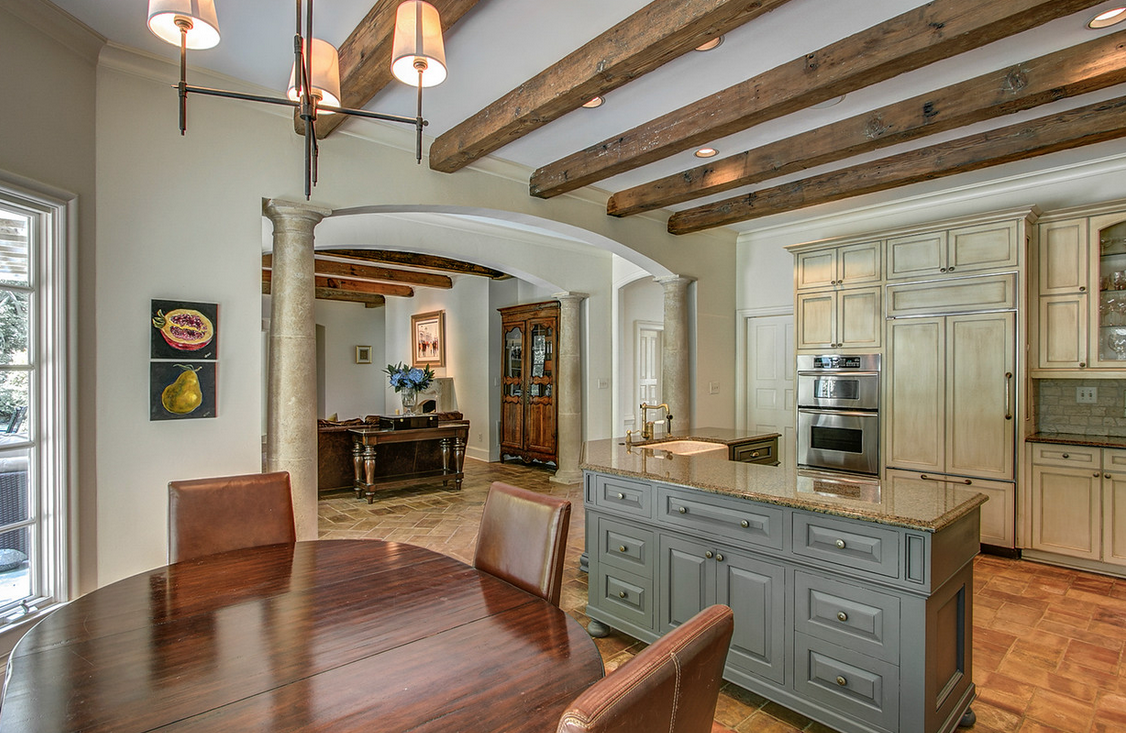 kitchen with beams and a dark island with light cabinets
