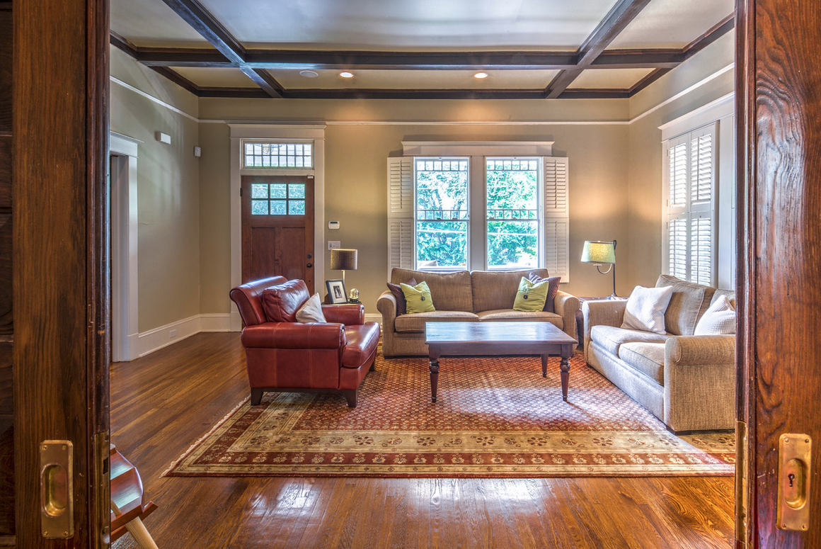 Craftsman living room with beamed ceiling and fireplace