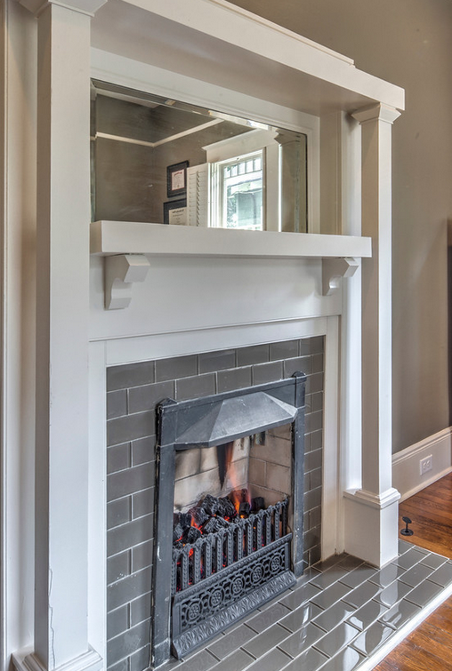 Grey and white fireplace craftsman style with a mirror