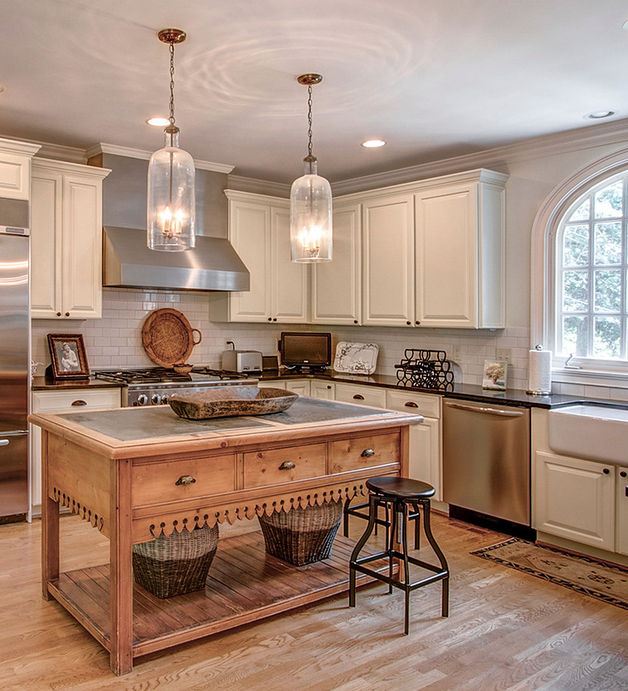 white kitchen with center island and arched windows