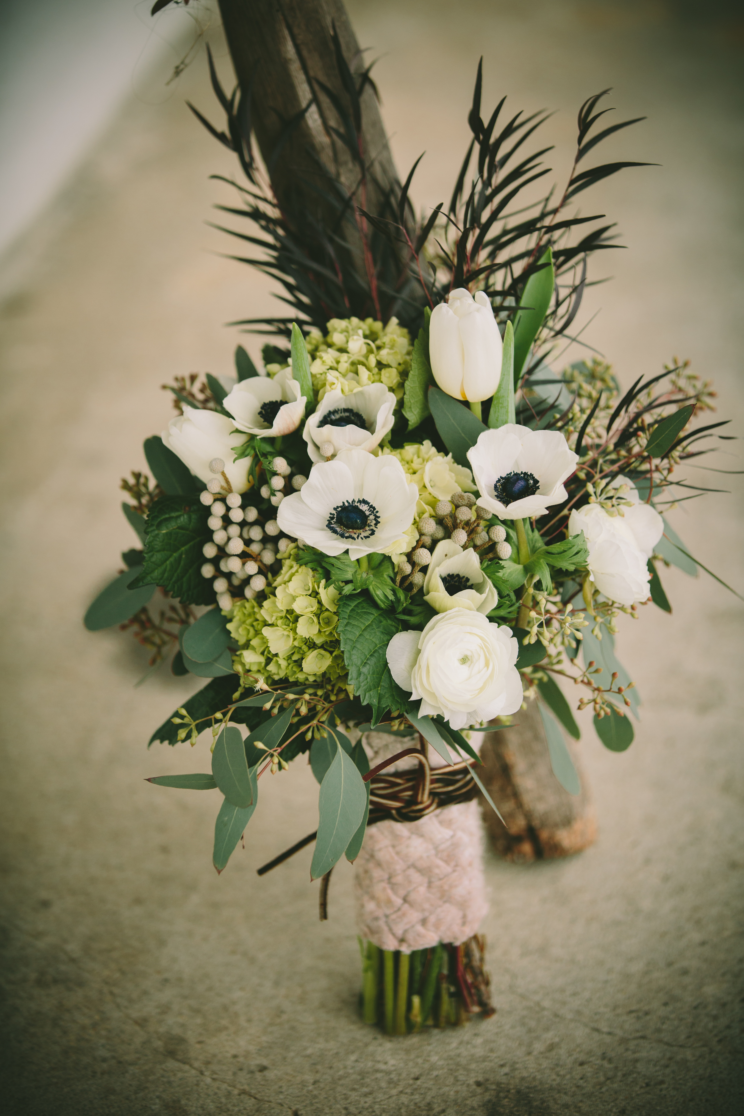 Bouquet wrapped in a vintage cable knit sweater tied with leather cord.