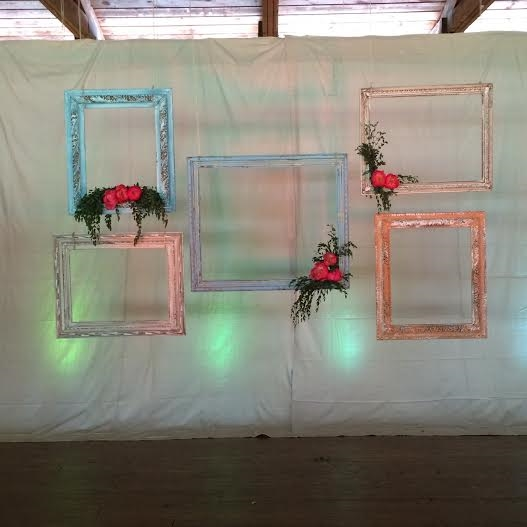 The altar and photo booth setting. Vintage frames strung from the pavilion rafters.