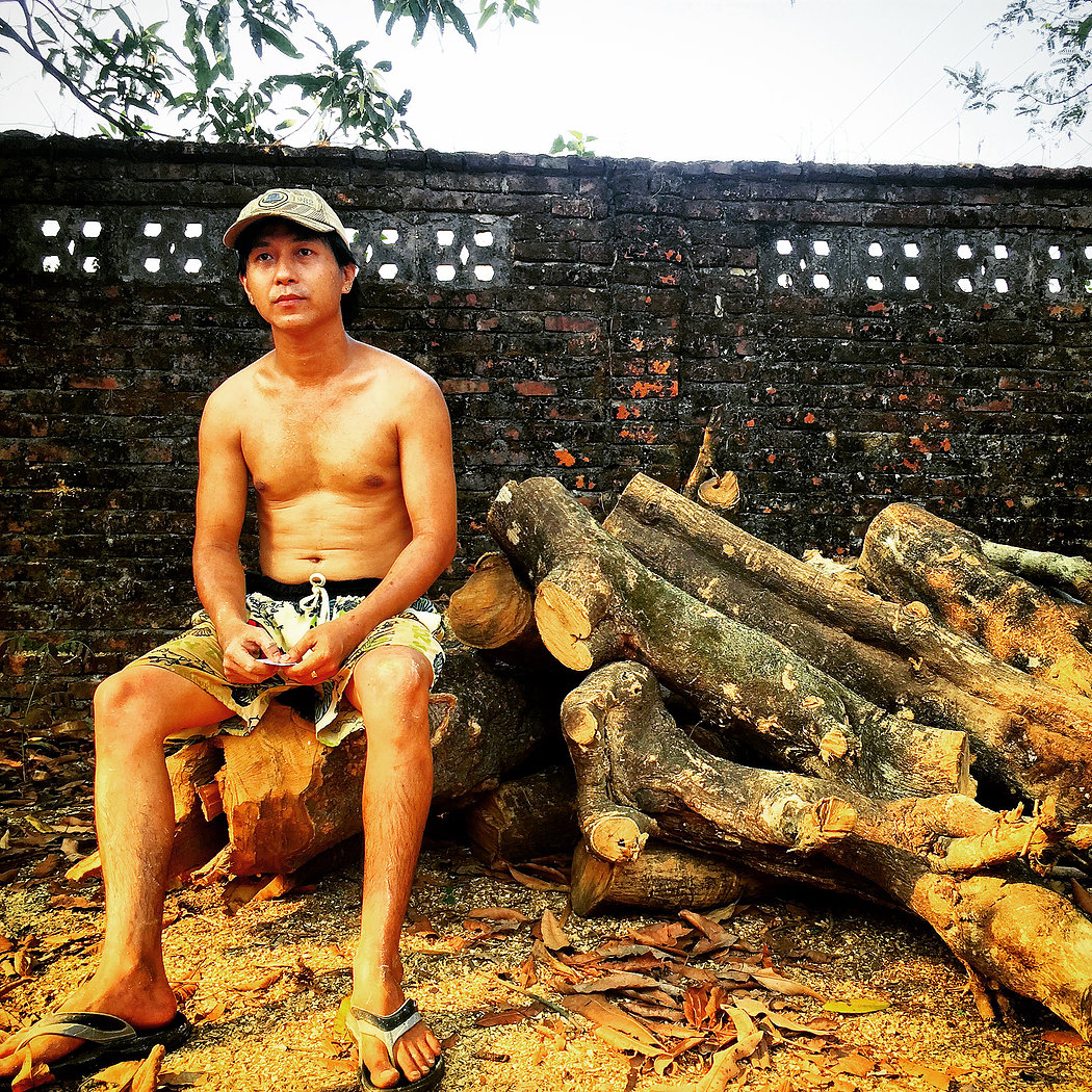 Kyaw Myoe Naung sits on Thanaka logs ready for processing at the factory. He is the grandson of this Thanaka company's founder in Mawlamyine, the capital city of Mon State.