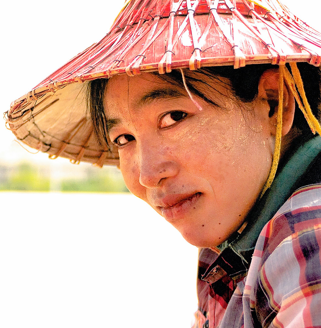 Ma Ni Myint glances over as she takes a pause from work. She likes to wear thick stripes of Thanaka paste on her cheeks, but by late afternoon most of it wears off from the extreme summer heat.