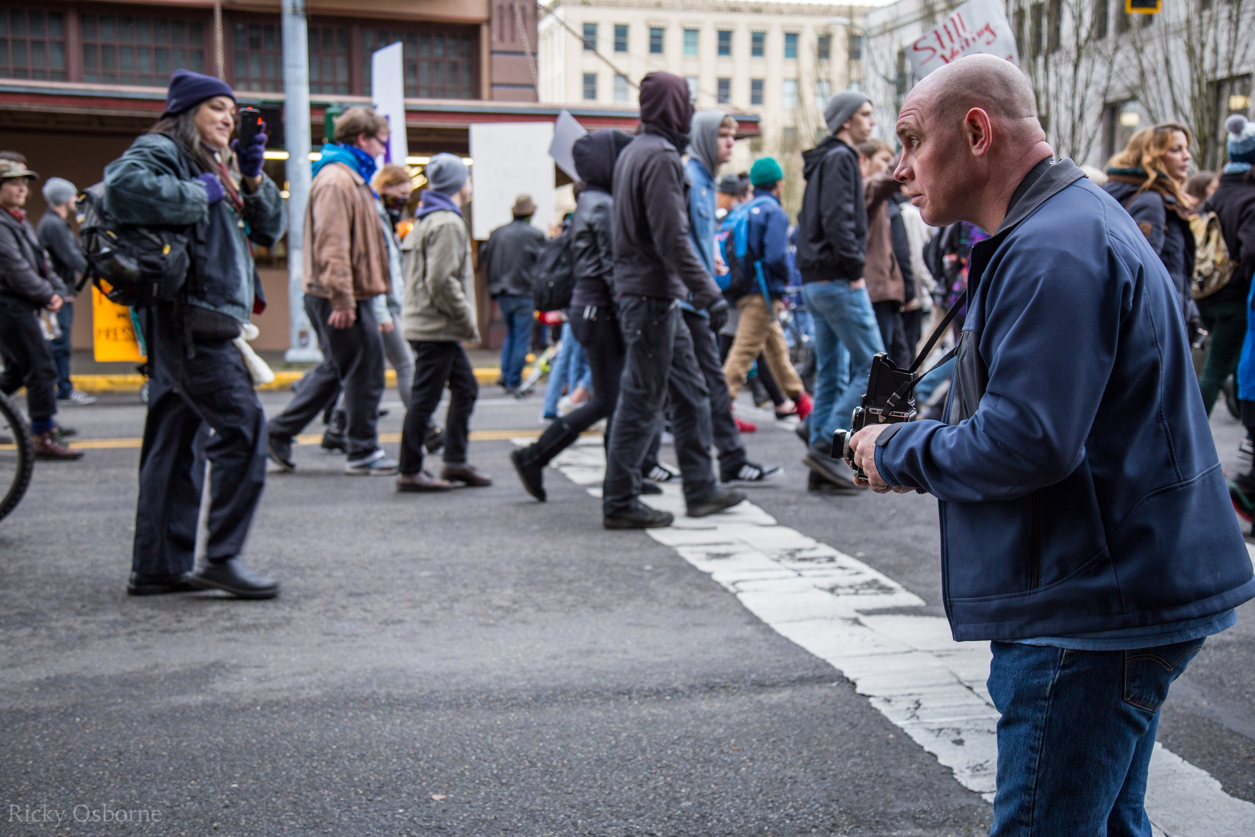 A photographer uses a medium format film camera to shoot a scene from the march.