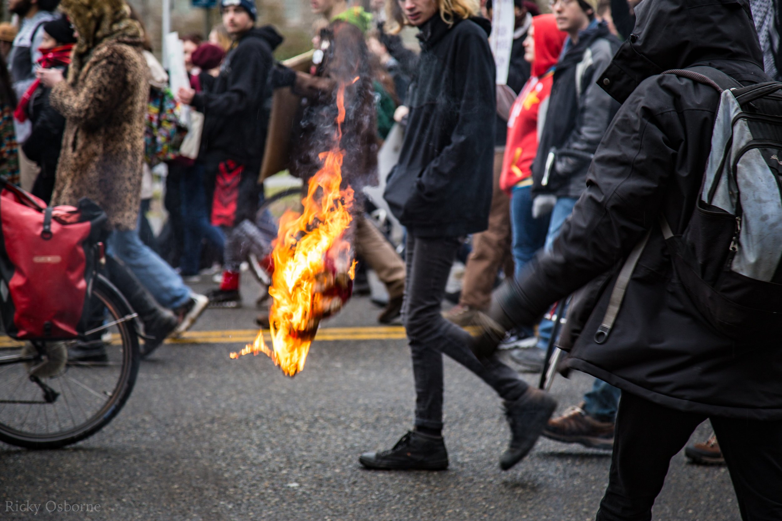 A fiery American flag floats through the air as protestors march.