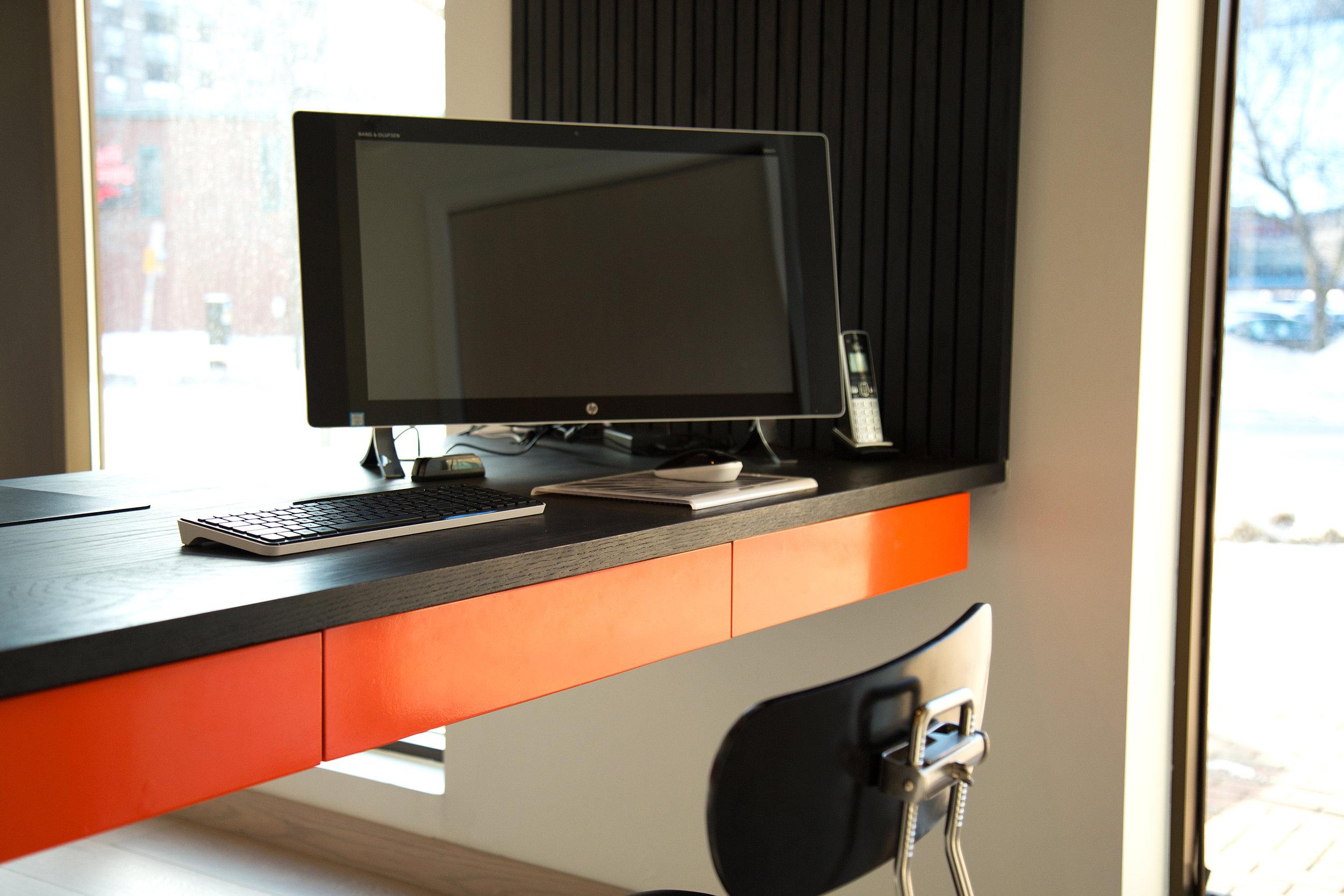 Bright orange drawer fronts underneath desk top