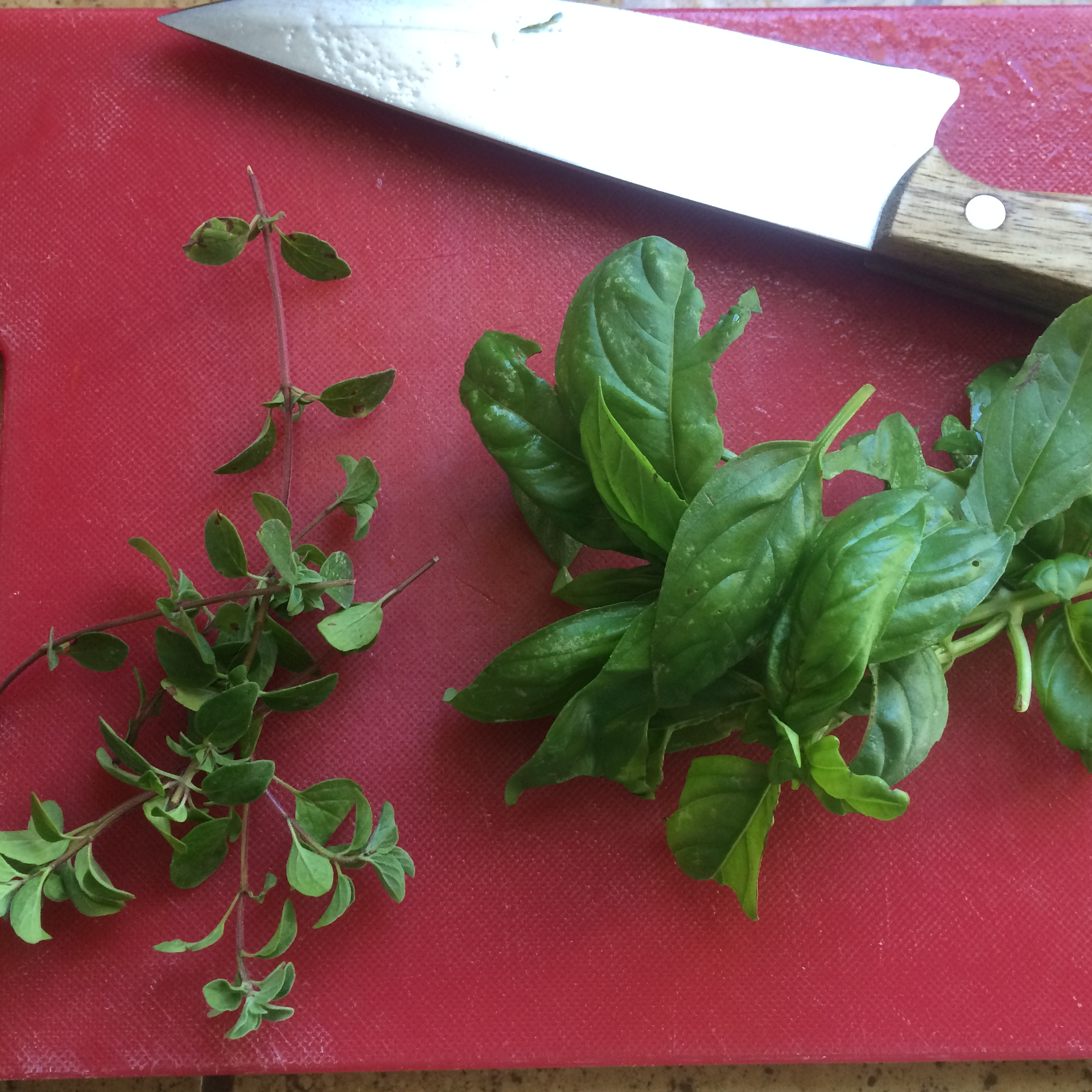 Wash and finely chop the fresh oregano and basil.