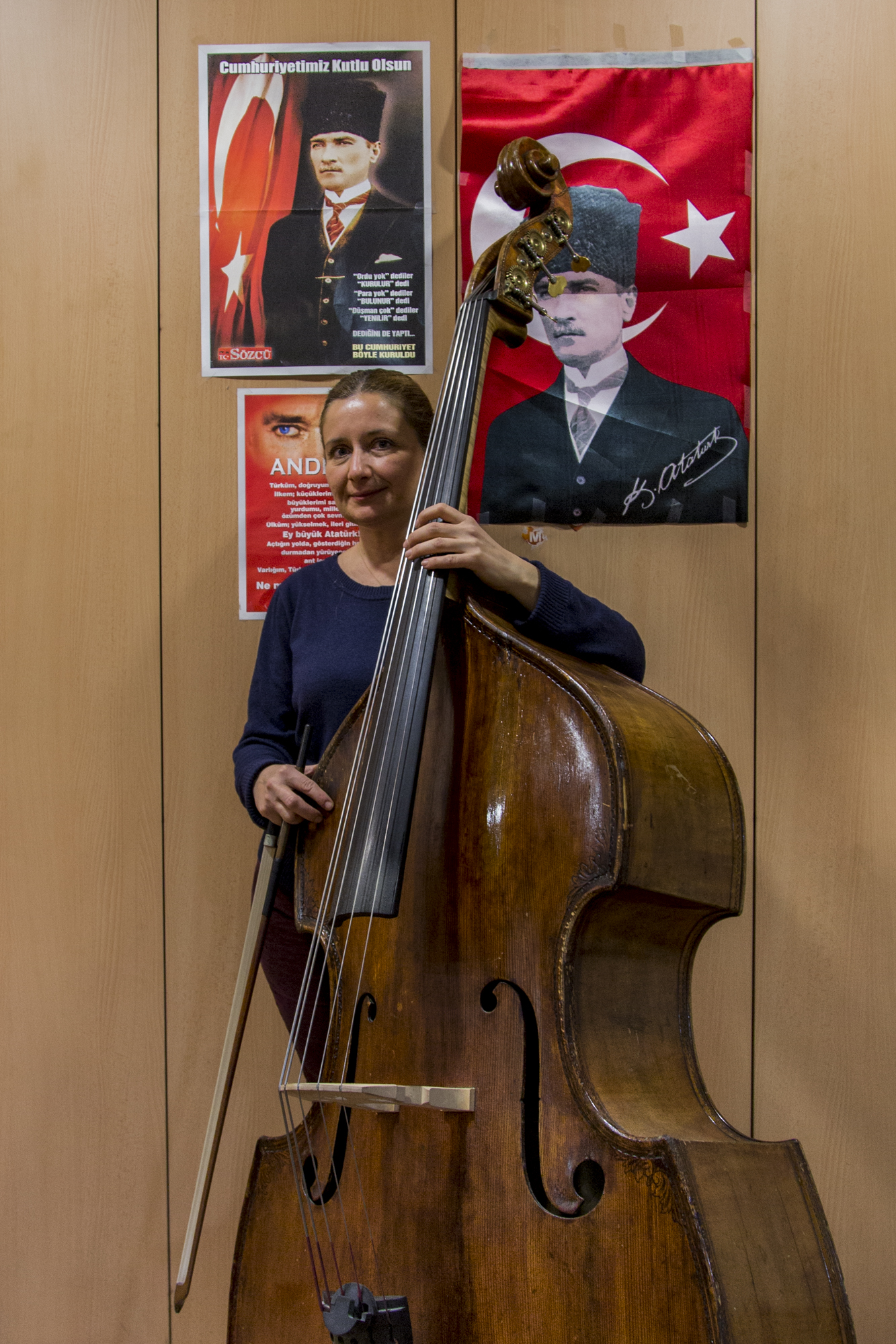 Aylin, a bassist poses in front of her locker decorated with many posters of Atatürk, the founder of the Republic of Turkey, during a break in rehearsals. Ankara, 18th of December 2014.