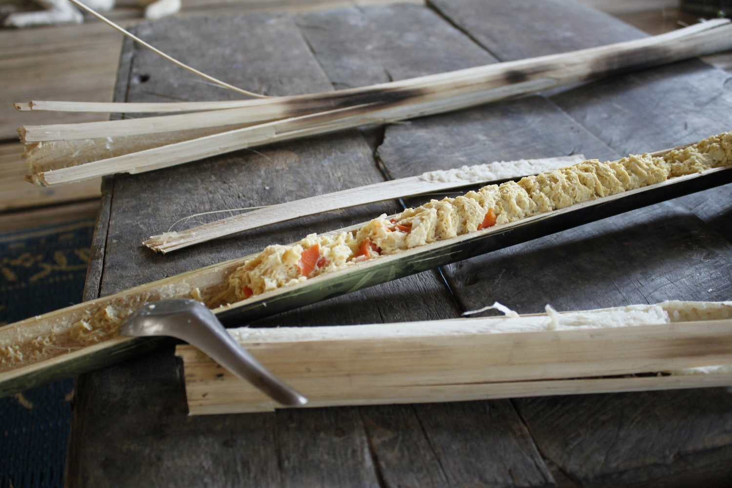 Sticky rice, eggs and vegetables cooked inside pieces of bamboo