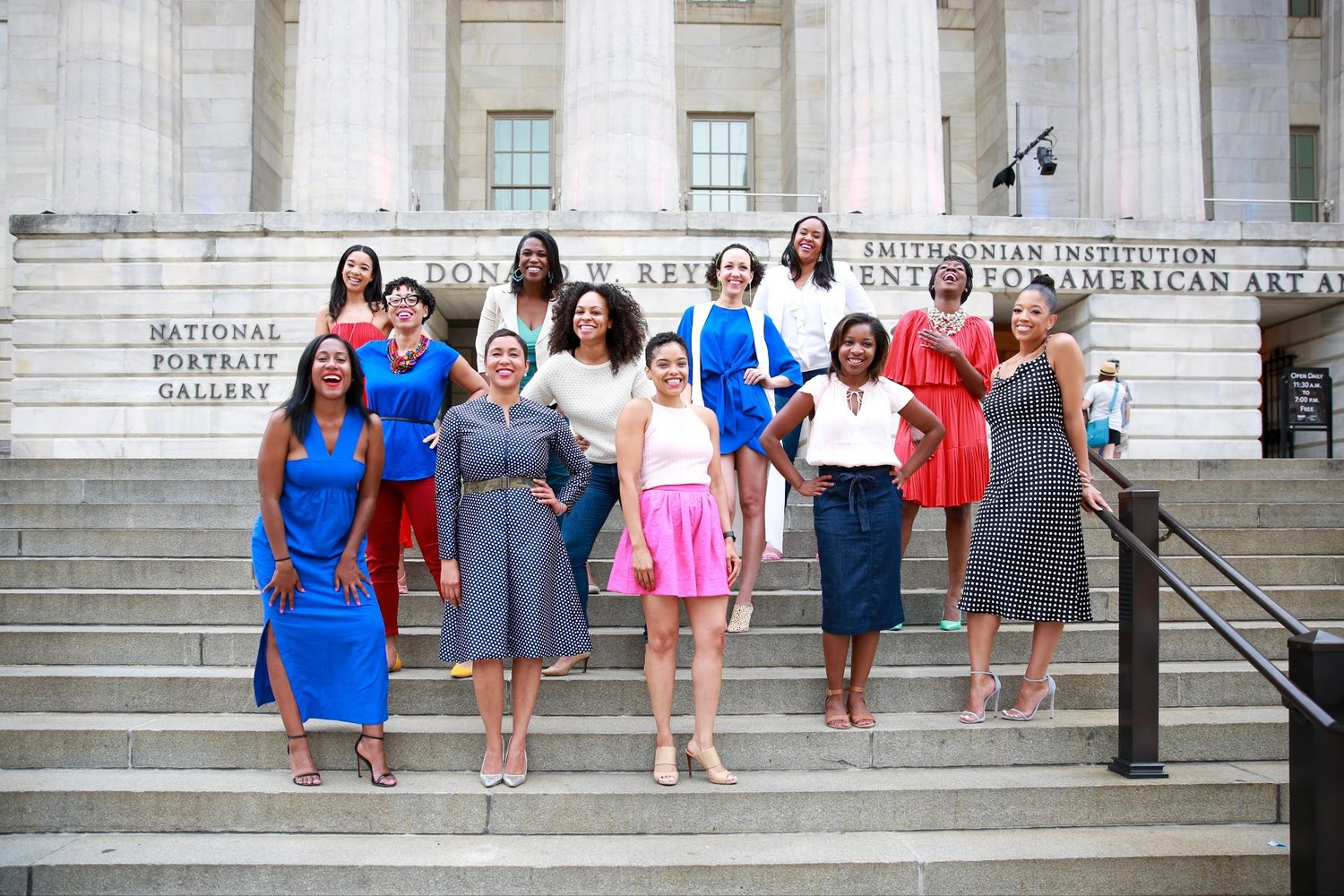 12 Black women standing up laughing on steps outside the National Portrait Gallery in Washington, D.C.  Photos:  Milli Mike / Millgrimage
