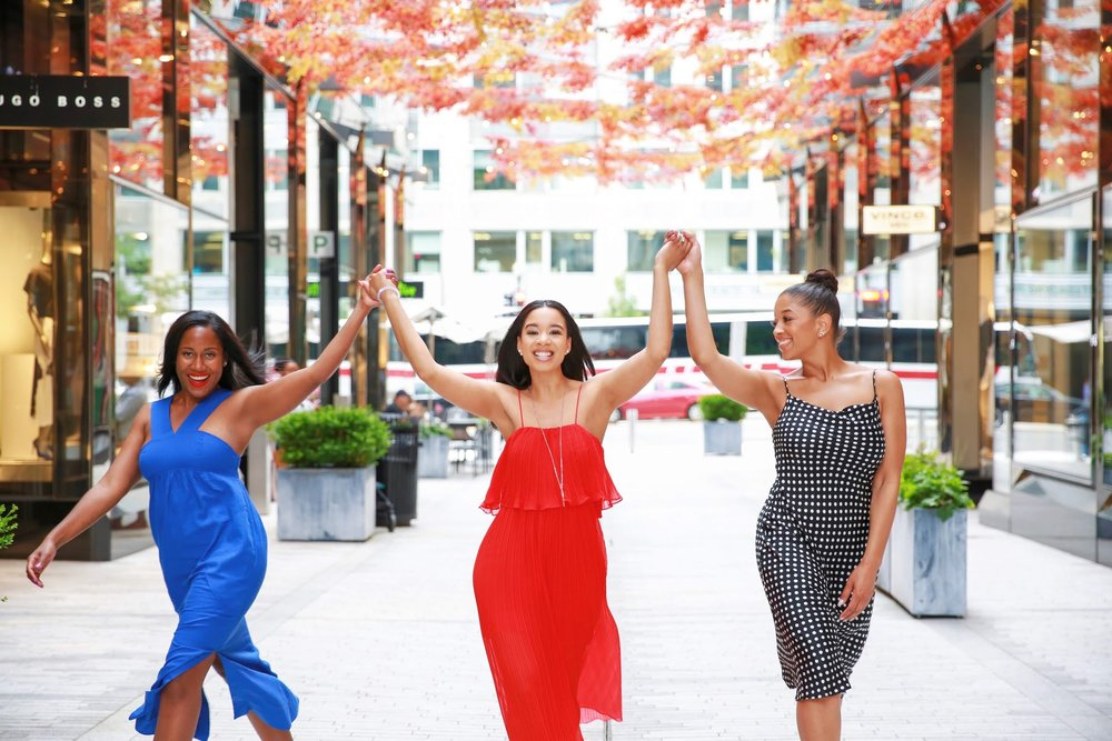 3 Black women smiling holding hands facing the camera in City Center, Washington, D.C.  Photos:  Milli Mike / Millgrimage