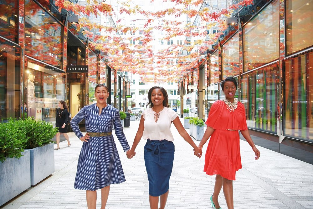 3 Black women holding hands facing the camera in City Center, Washington, D.C.  Photos:  Milli Mike / Millgrimage