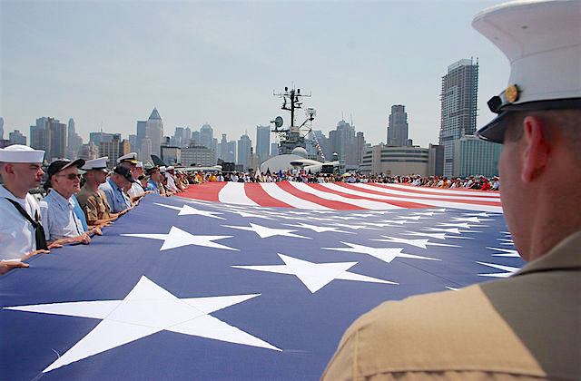 New York (May 29, 2006) - Marines, Sailors, Soldiers, Airmen, Coast Guardsmen and military veterans display the American flag during the playing of taps on the deck of the museum and display ship USS Intrepid, during a Memorial Day Commemoration at Fleet Week
