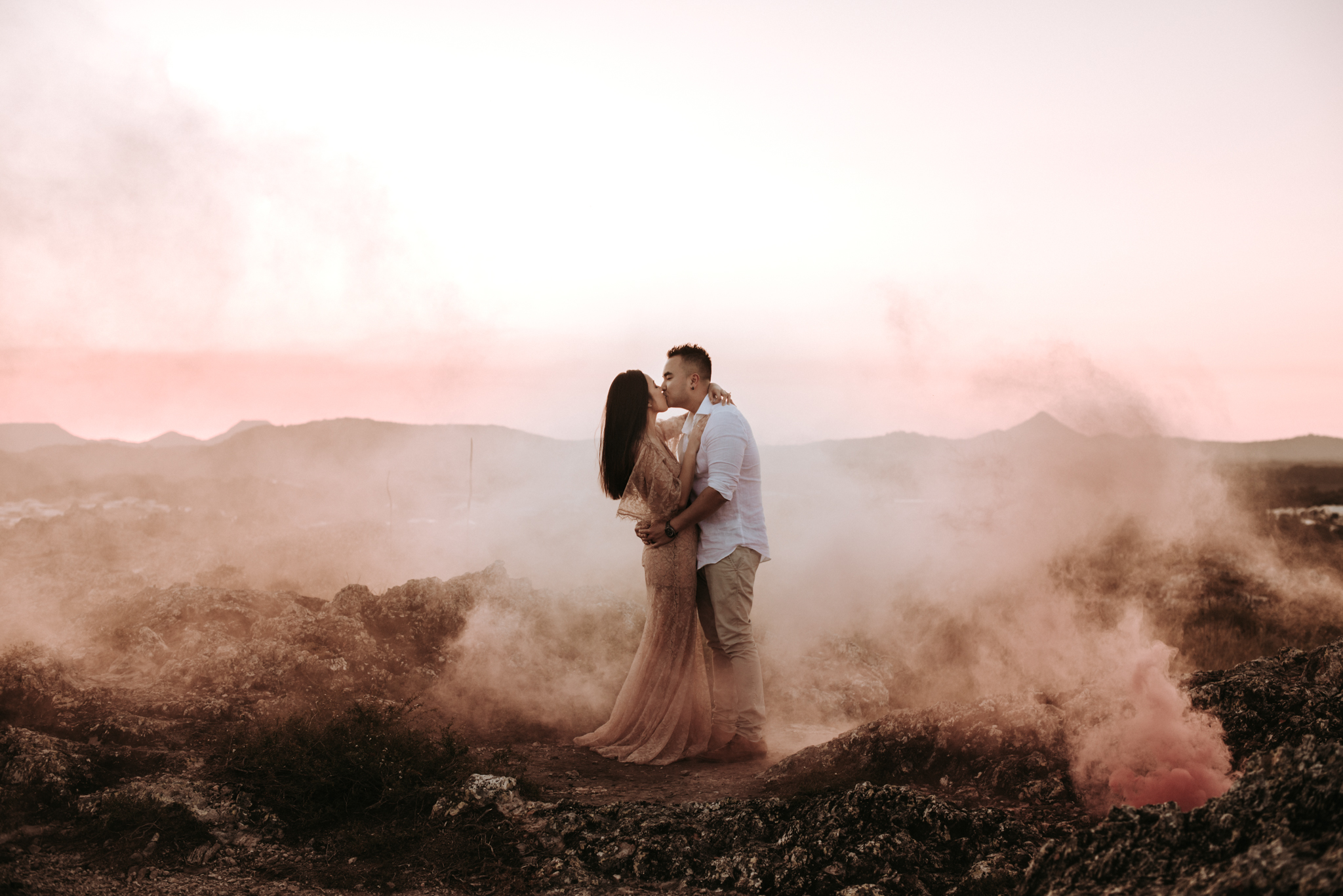 Red Smoke + Mountain Sunset - The smoke delivered from red smoke bombs turns out to look quite pink and it's the perfect shade to enhance the beauty of a peachy sunset. We ran back and forth behind our couple, Viv & Dong, a few times to create a wall of smoke first and then placed the smoke bomb on a rock surface to emit additional thick smoke next to them without blocking the couple or the mountain range in the back. Exposed locations like this one work best if there is just a gentle breeze and no strong winds, so check the weather before you start climbing.