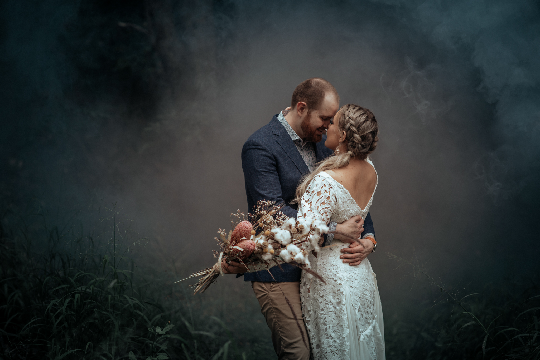 Green + Blue Smoke in the Woods - We chose an enclosed forest section by a creek to trap thick green and blue smoke around our couple, Jacqui & Chris. It was a rainy and overcast day and the smoke lingered around perfectly. Again, we initially ran around behind the couple to create a wall of thick smoke and then stood to the side with the smoke bombs to add some more, walking across every now and again to keep the wall of smoke up behind the couple. This was shot at noon for a first look in natural light.