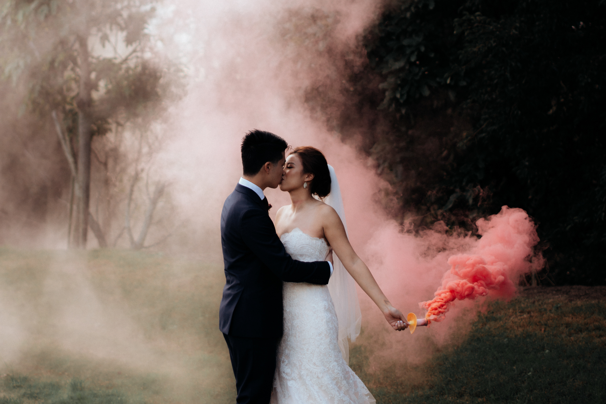 Red Smoke against Green Backdrop - This photo was taken back in the day when we still permitted our couples to hold the smoke bombs in their holder {more on that in below}, but I am sharing it anyways because it demonstrates the use of contrasting smoke to create movement and colour.The couple was placed against a darker backdrop of a forest to make the smoke and wedding gown stand out. It was a red smoke bomb, emitting pink smoke. Photographed at sunset with some magical light peeping in from the left.