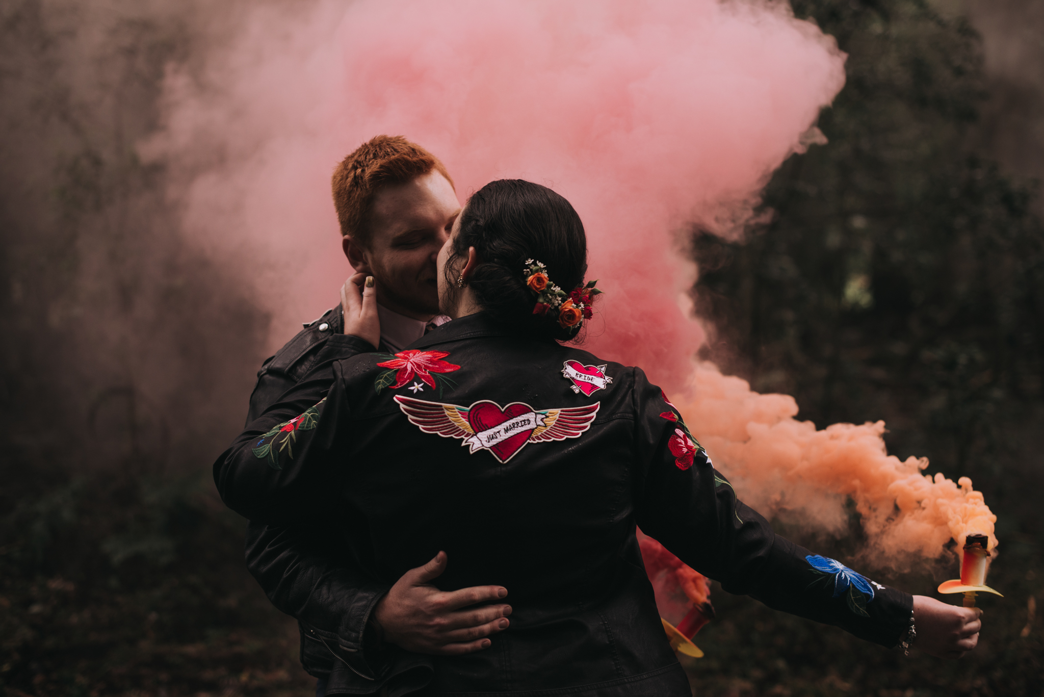 Orange + Red Smoke Bombs in the Woods. Please note that this photo is a few years old and that we don't allow our couples to hold the smoke bombs anymore.