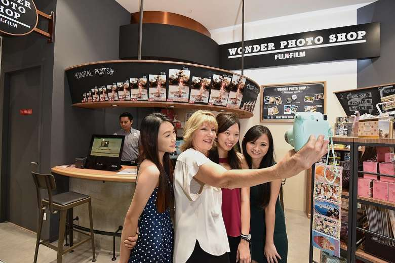 Harvey Norman chief executive Katie Page (second from left) posing for a wefie on Thursday with staff (from left) Gina Chan, Samantha Wong and Fiona Low at Singapore's first Fujifilm Wonder Photo Shop in the new Harvey Norman store in Millenia Walk.PHOTO: DIOS VINCOY JR FOR THE STRAITS TIMES