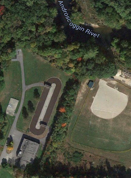 The Mechanic Falls Sanitary District WWTP is sandwiched between downtown businesses and a community sports field. Its primary systems are enclosed (building at lower left) and secondary treatment is in an oxidation ditch (oval shape). Clean water is discharged to the Androscoggin River and lime-stabilized biosolids are applied once a year on a local farmer's fields.