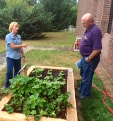 Kristin Noel (left) shows off the new raised garden beds at the Concord Treatment Plant. Biosolids soil fills the beds, growing flowers and vegetables.