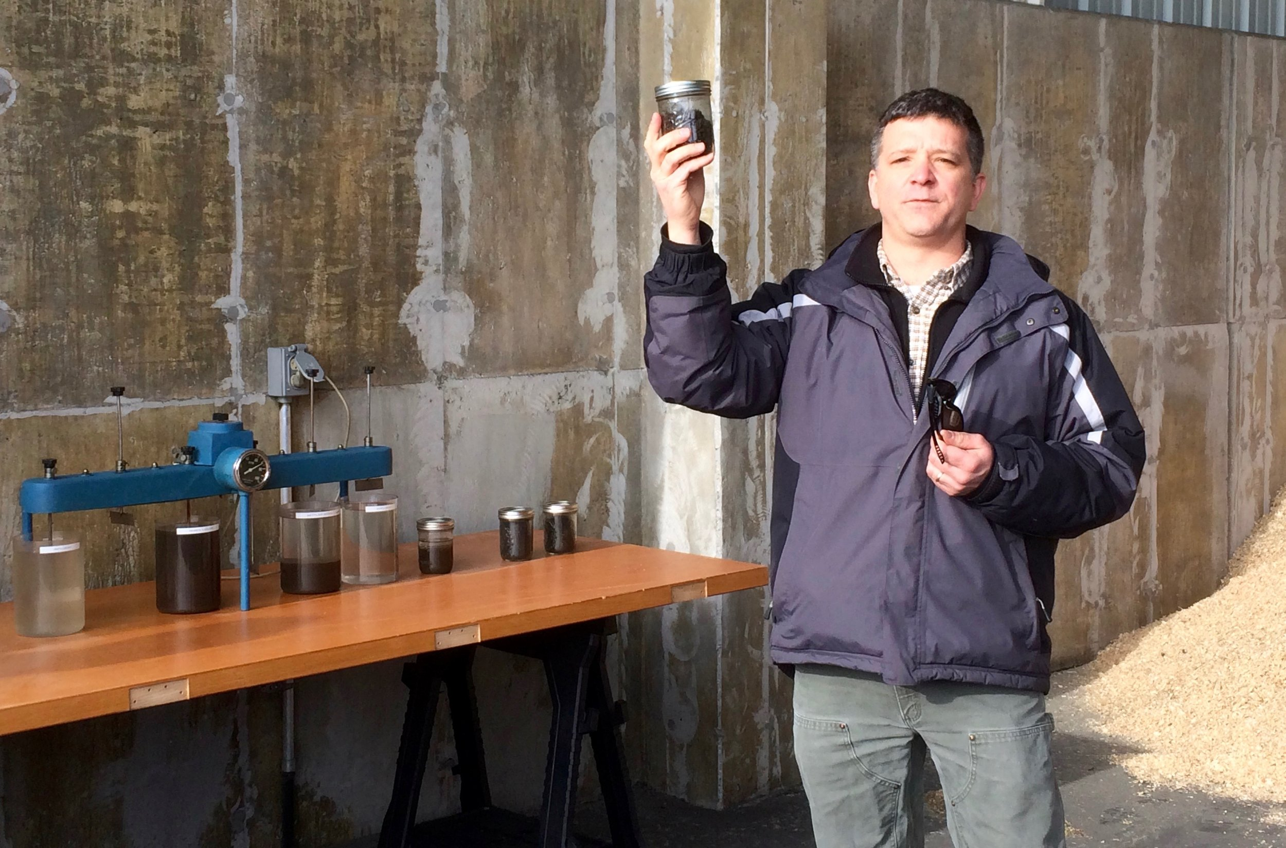 Andre Brousseau, Superintendent of Sanford Sewerage District, shows a sample of dewatered wastewater solids that go into the biosolids compost. To the left is a model of the wastewater treatment process that produces the solids.