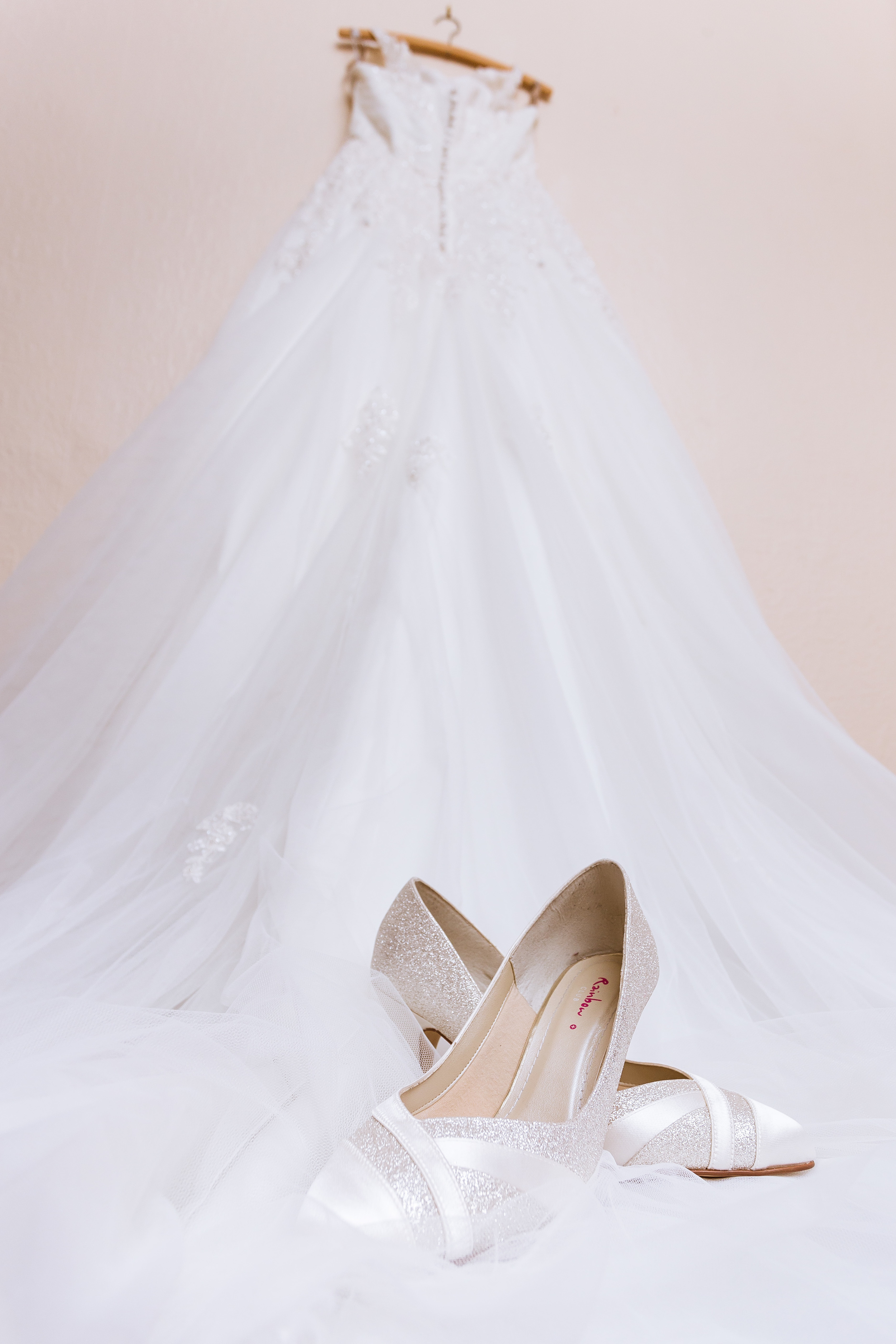 Silk and lace Bridal High heels placed on top of her wedding dress, the sweep of the dress pulls you down to the shoes
