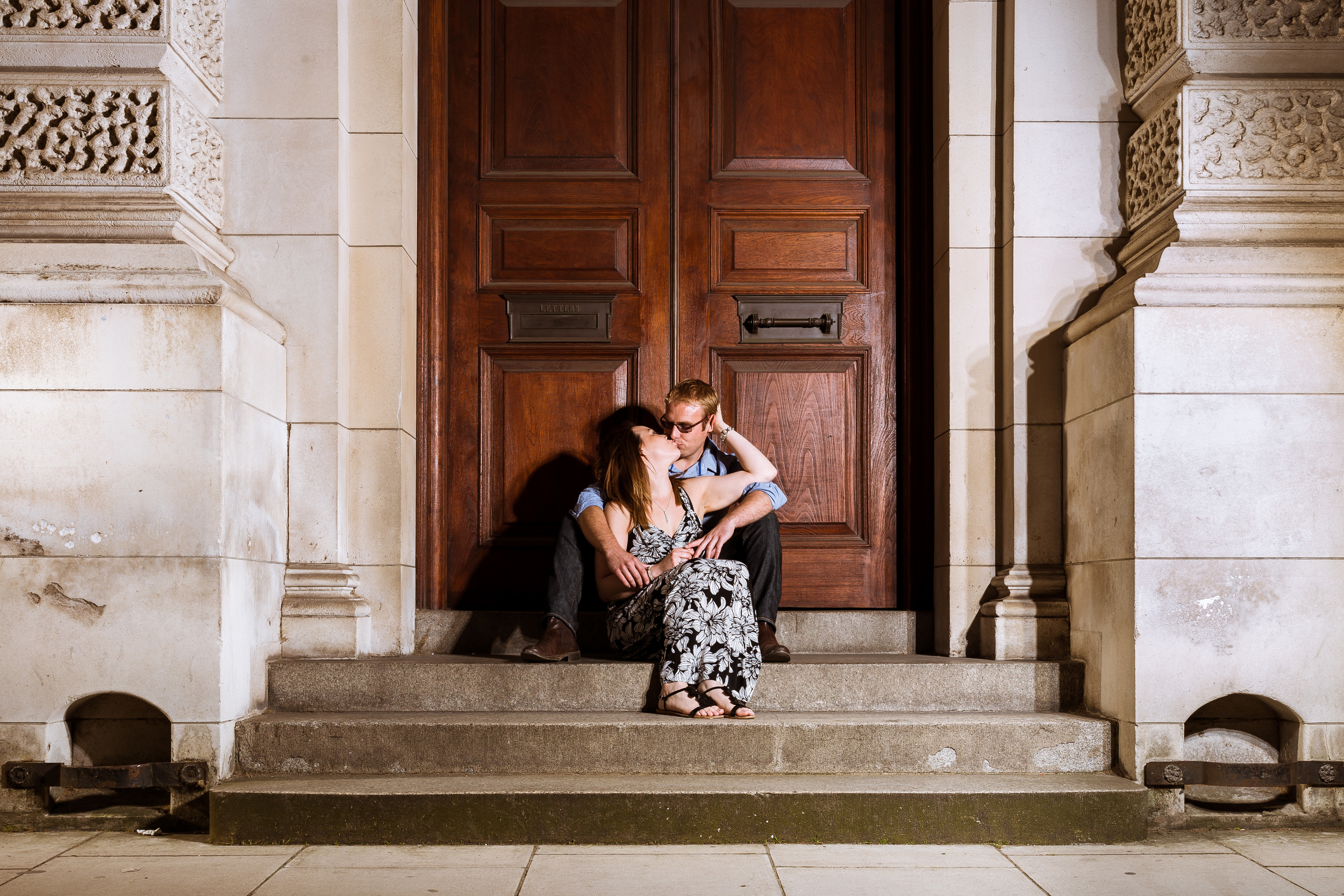 Sarah and Marc are sitting on a step in London while they were on their engagement shoot, it has been lit from a light on the right. Their session lasted around 3hours this was done before their wedding at dale hill golf club in East sussex