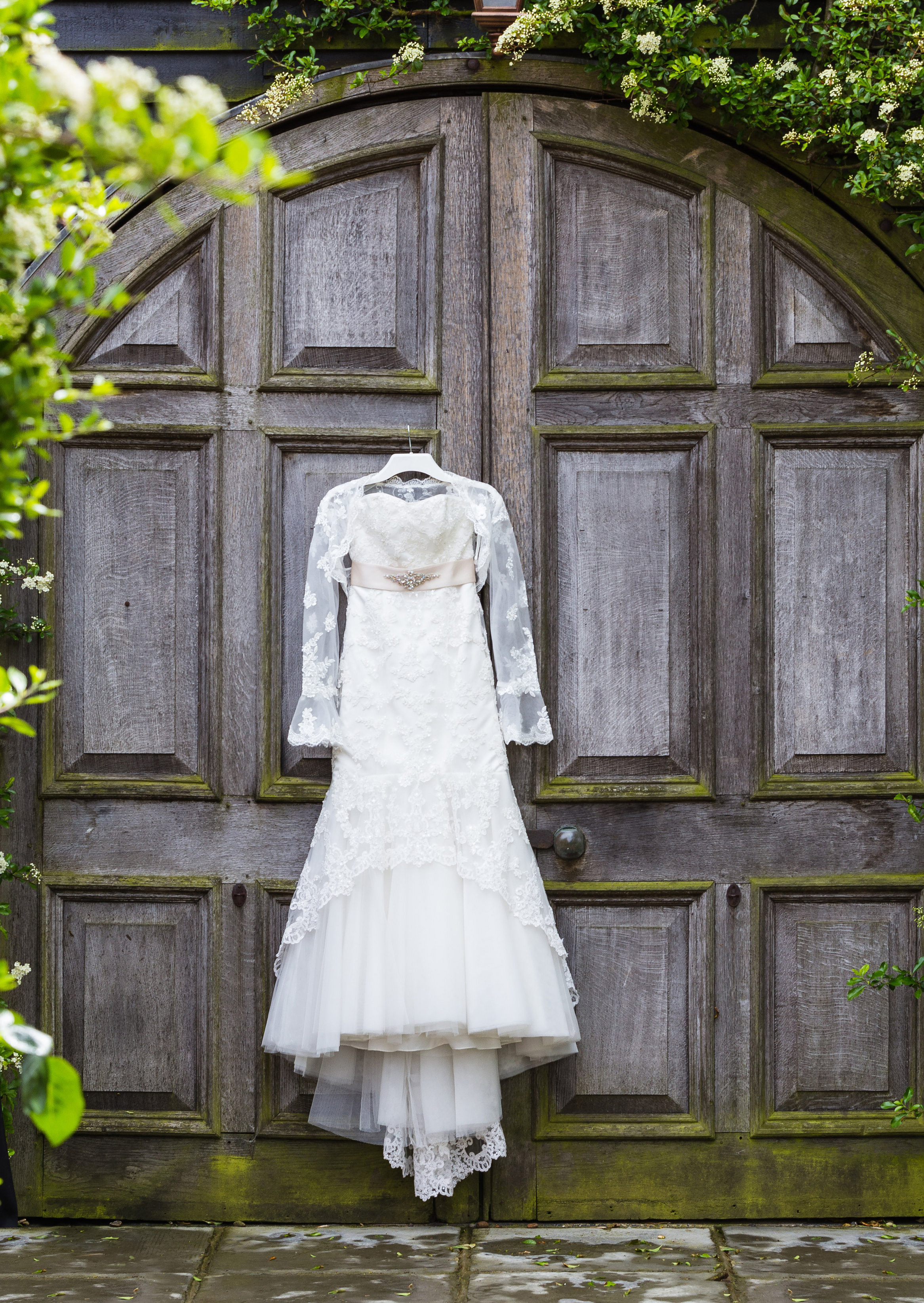 A White Wedding Dress hanging on a barn door at winters barn in canterbury