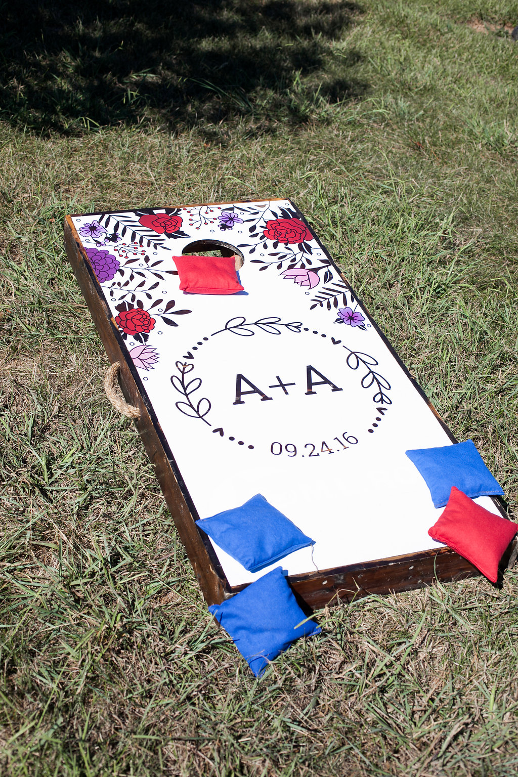 Cornhole board: Logo matched to the wedding cocktail napkins. Printing and vinyl installation by  Big Visual Group .