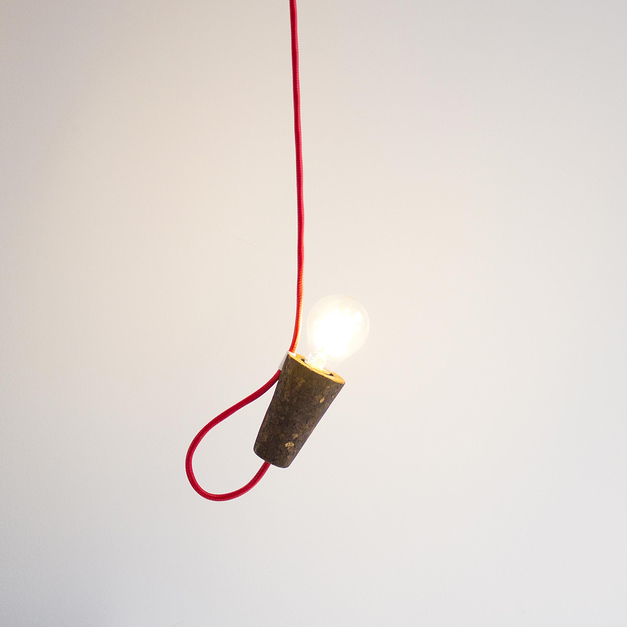 'Sininho' pendant lamp - 'Sininho' pendant lamp, light or dark cork and red cable. The light spot can be directed up or down and you can use alone or with other 'Sininho' and form a chandelier.Candeeiro 'Sininho', cortiça clara ou escura e cabo vermelho. O ponto de luz pode ser direcionado para cima ou para baixo e pode ser usado sozinho ou com outros 'Sininho' e forma um candelabro.