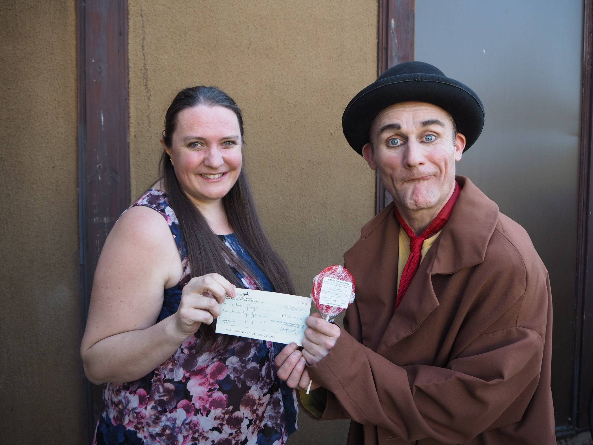 Tweedy of Giffords Circus presenting Sarah Avery, Manager of the Family Space with a cheque for £500