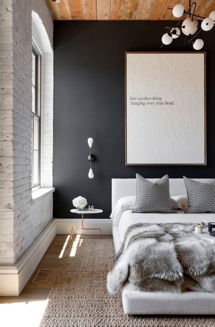 Love the exposed brick and wooden ceiling. Of course the faux fur throw and black accent wall as well!