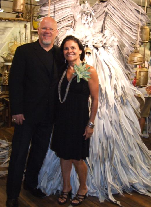 """Susan and Doug Williams in Kalalou's Atlanta showroom. The one-of-a-kind angel,   designed and assembled in house, is made of latex flowers (as is Susan's """"corsage""""), one   of the company's most successful introductions this year."""