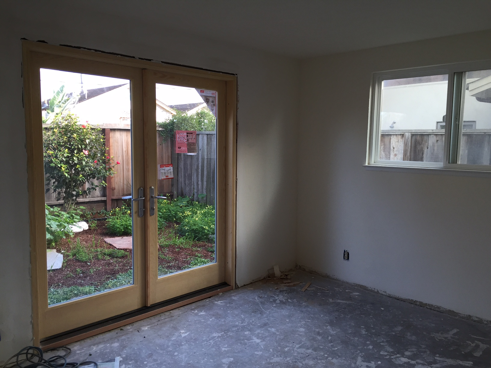 New Milgard french doors installed in the downstairs bedroom and the carpet ripped out.