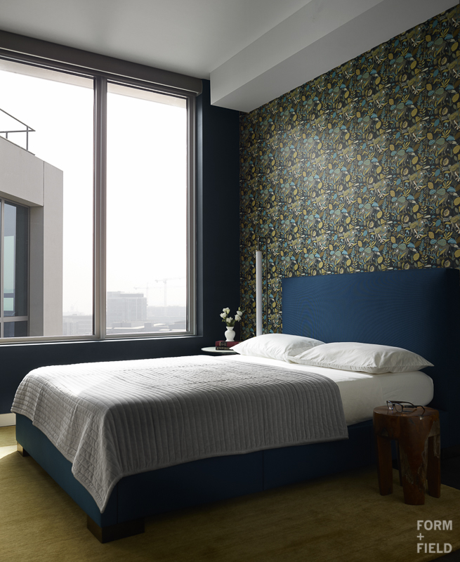 AFTER: We created a moody guest bedroom with Farrow & Ball Hague Blue paint and a patterned wallpaper.